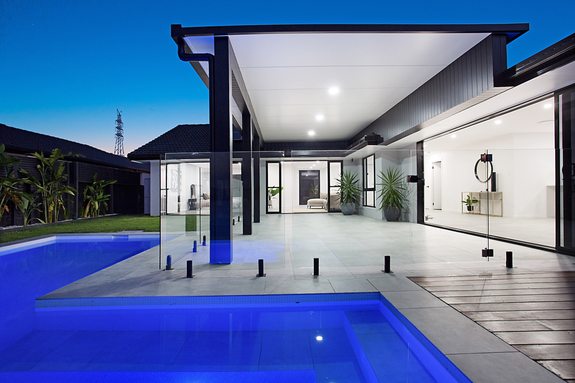 Outdoor entertaining space with a modern pool with white mosaic tiles and concrete flooring