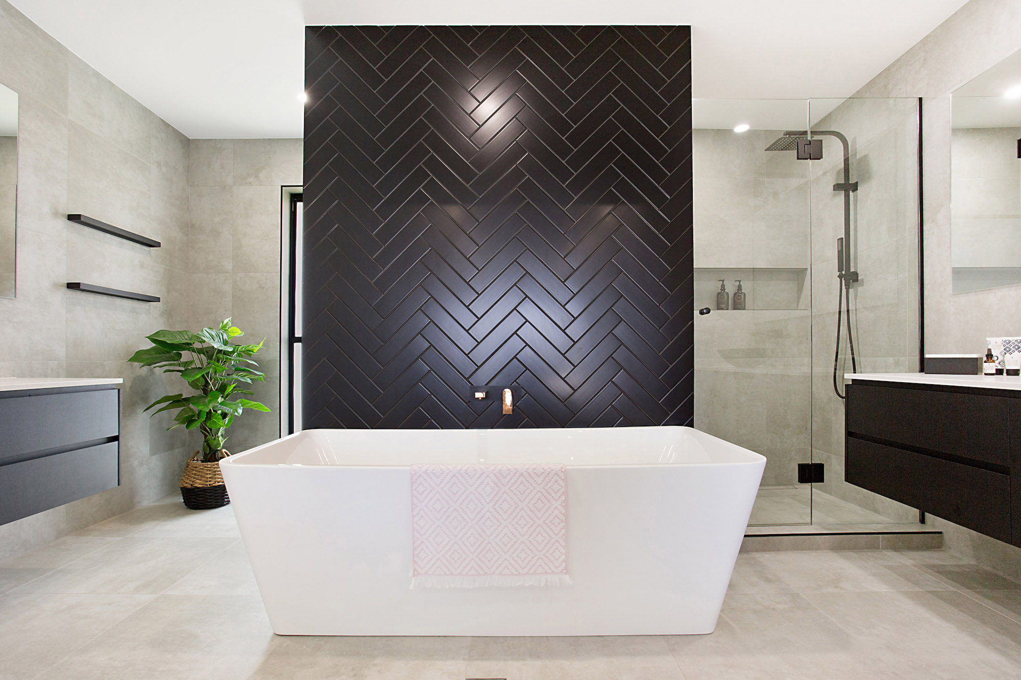 matt black herringbone wall in an exclusive his and hers bathroom as part of the master retreat