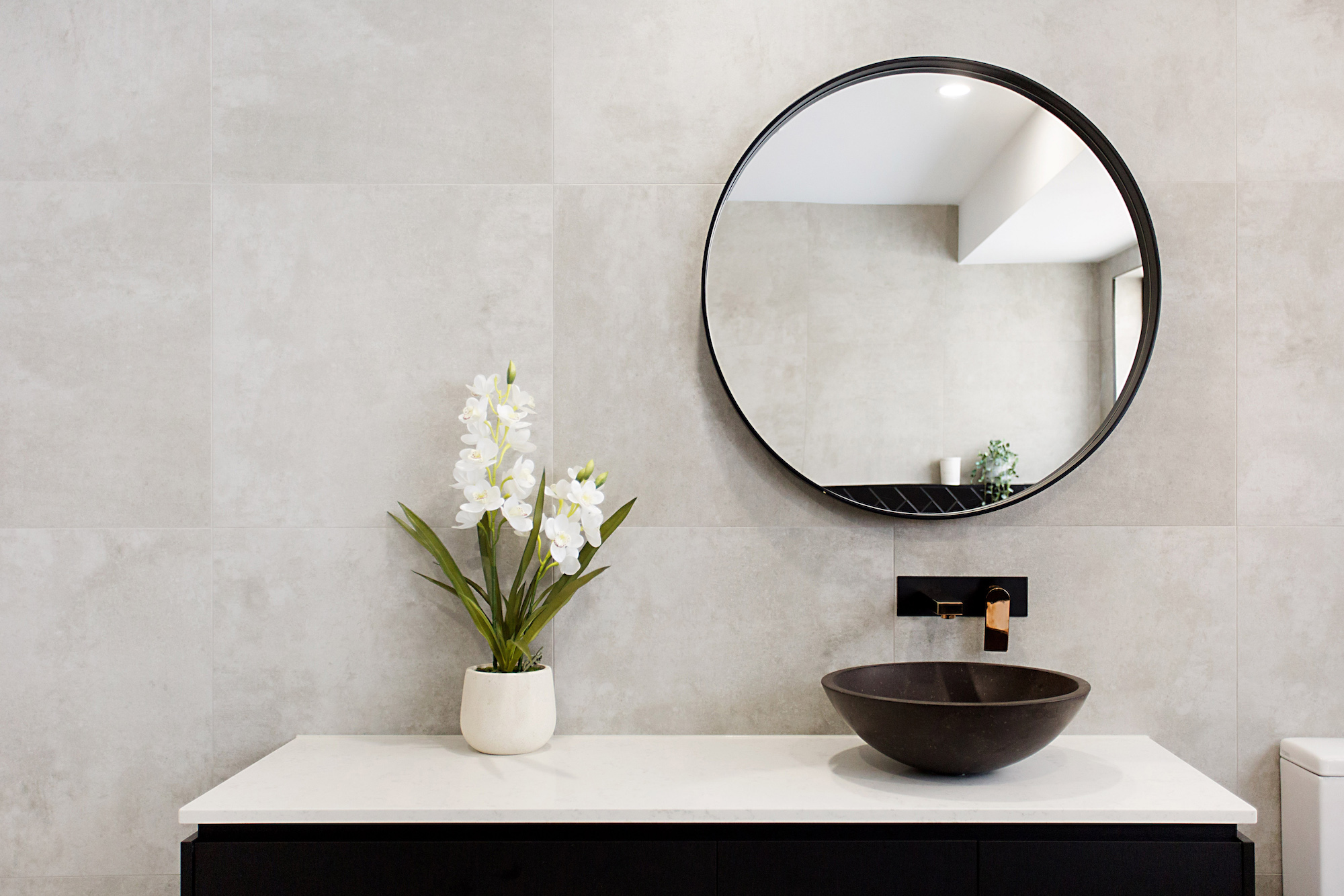 black round mirror in  a modern bathroom with grey tiles