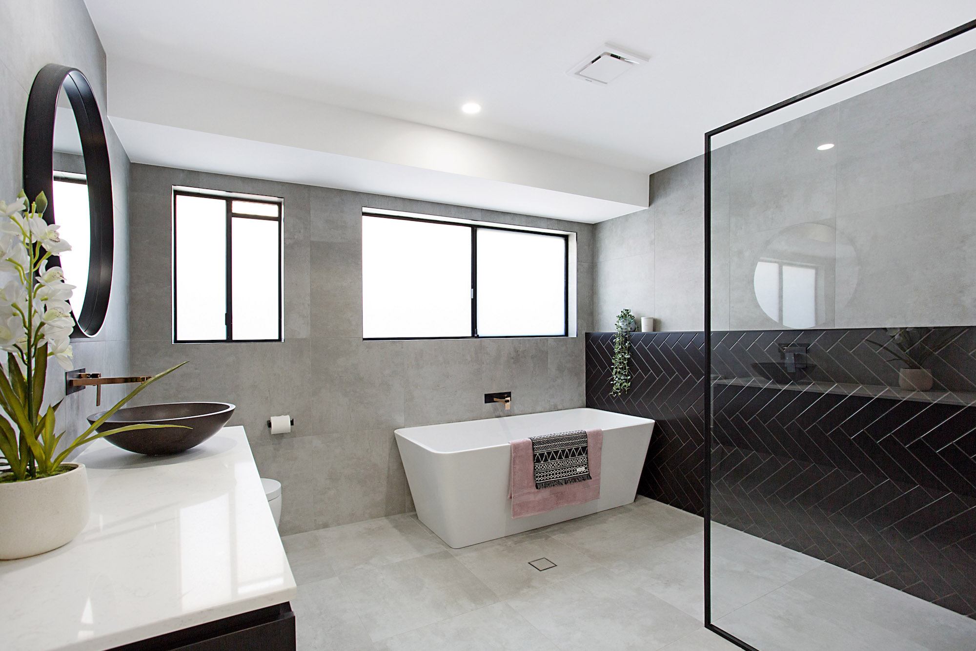 grey and black bathroom with herringbone feature and matt black taps and vanity