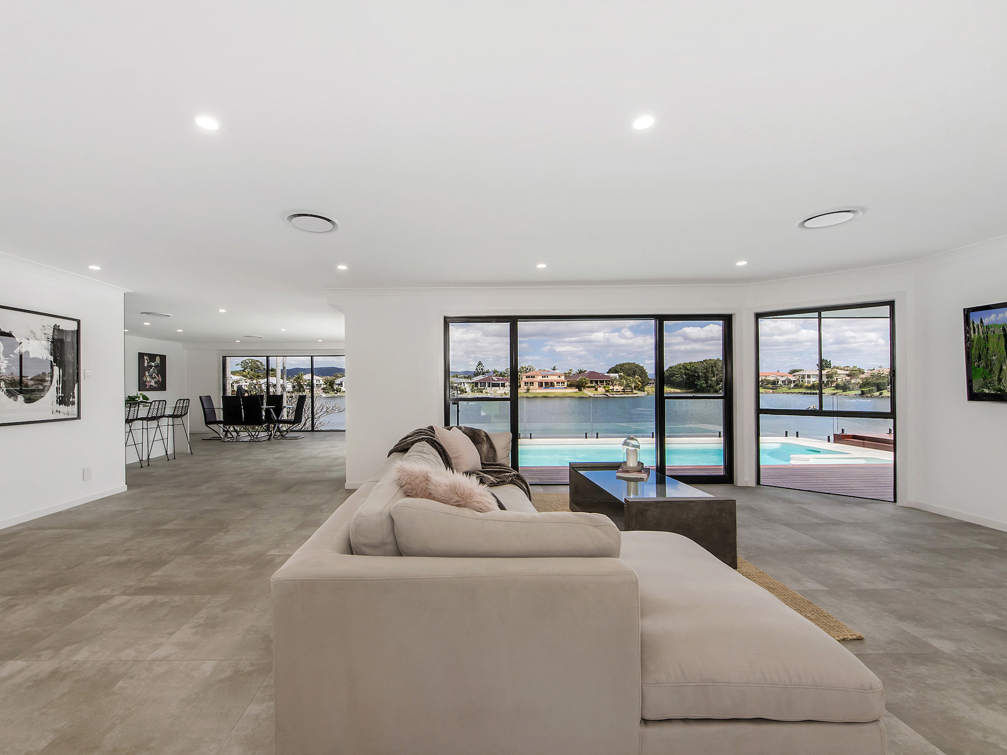 Open plan living dining and kitchen space surrounding the tiled pool