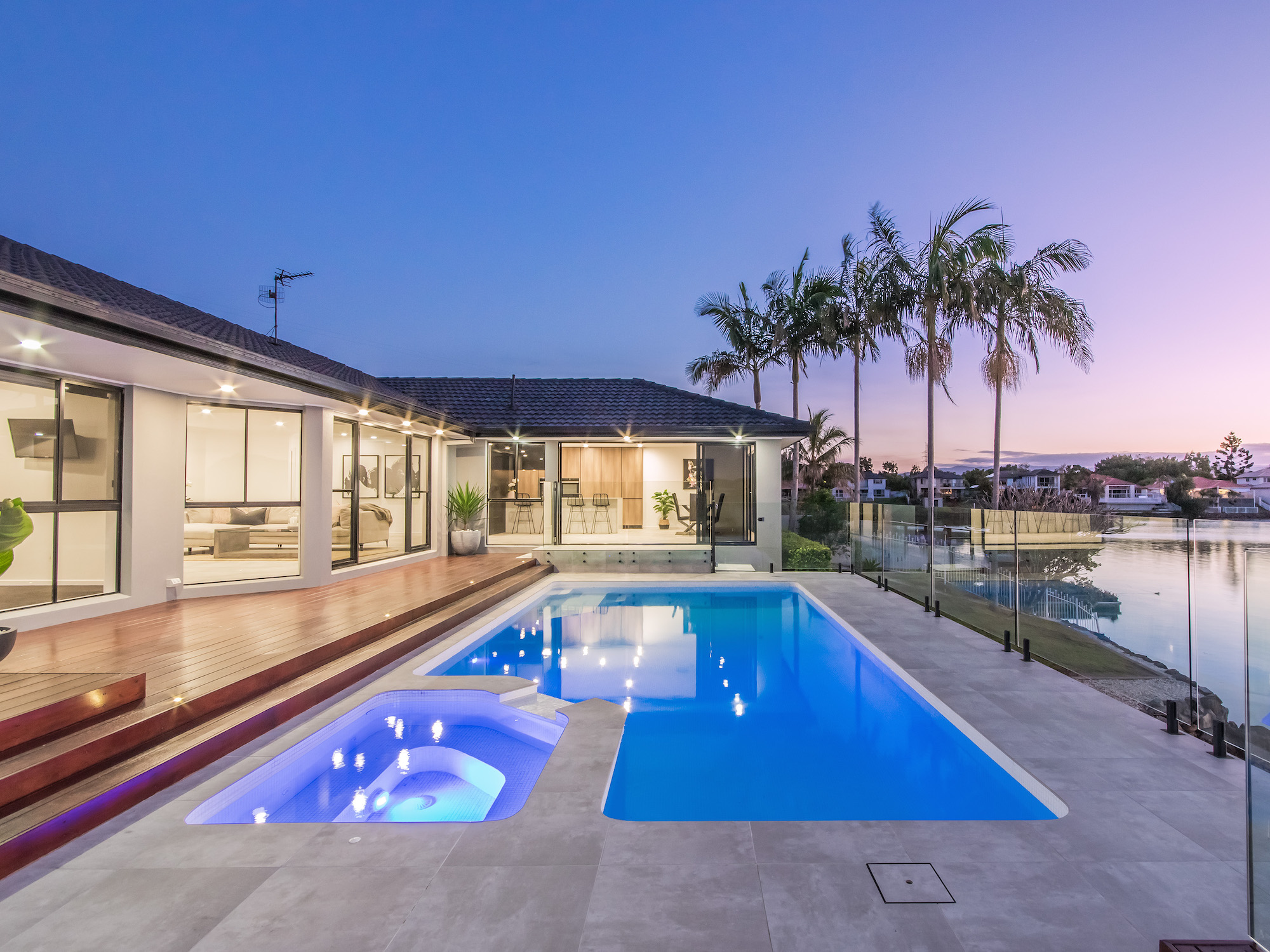 white tiled pool with spa and feature lighting overlooking a Gold Coast canal