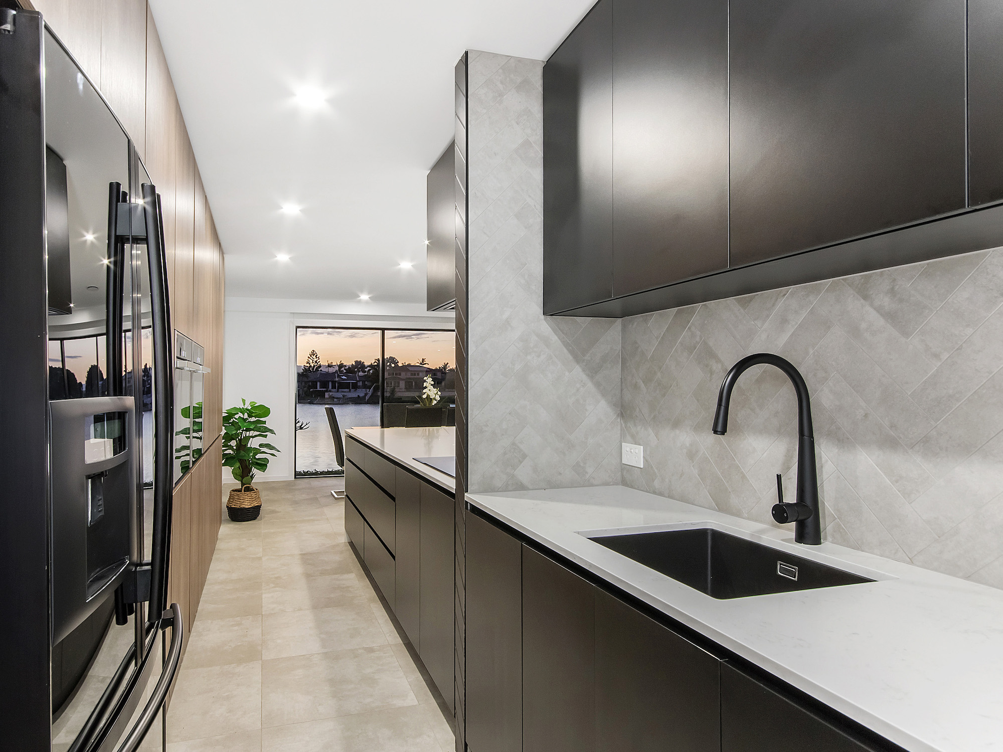 Modern concrete herringbone tiled splash back  with black kitchen sink and tap