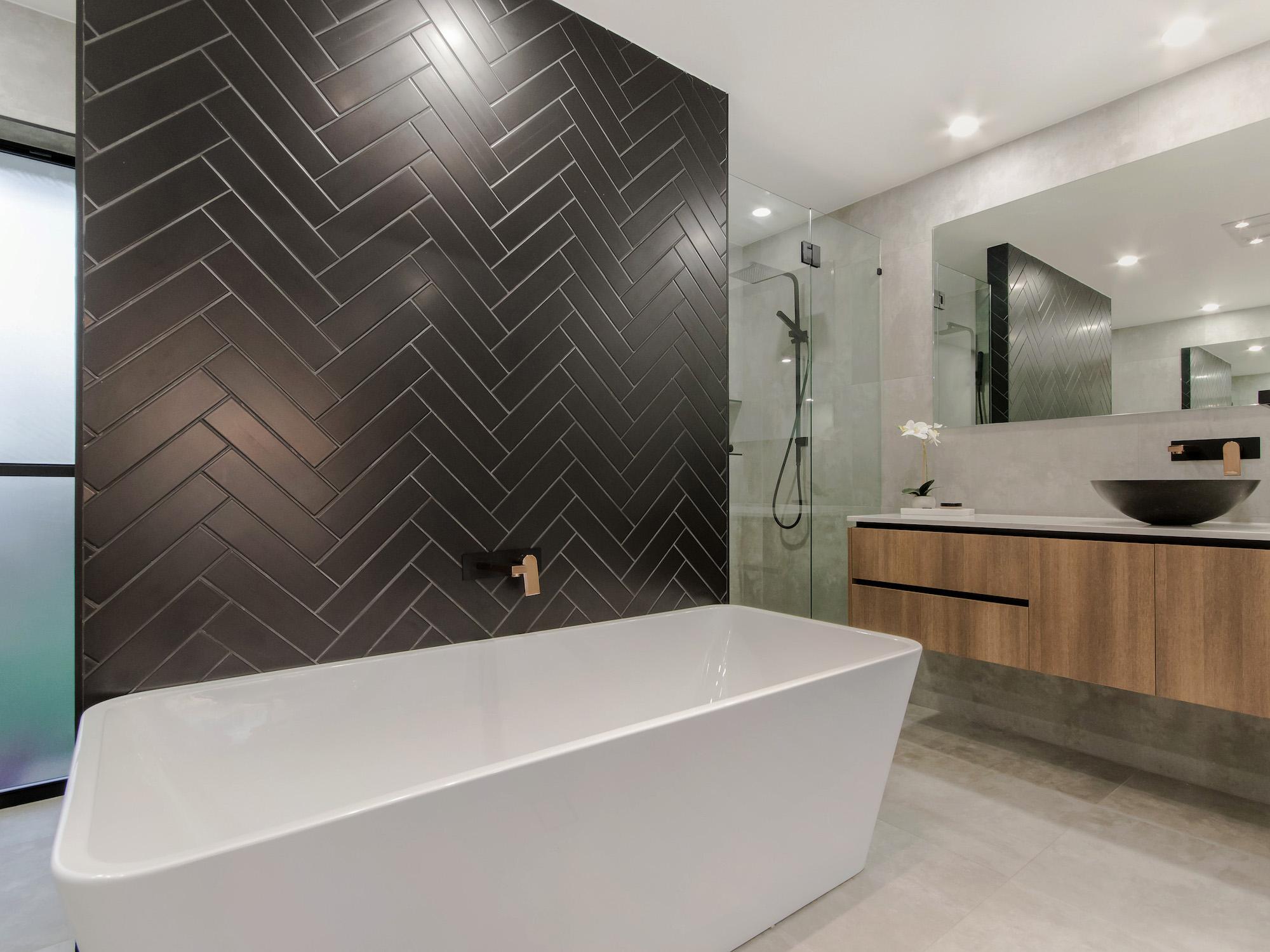 modern bathroom with black herringbone feature bath wall and custom made vanity