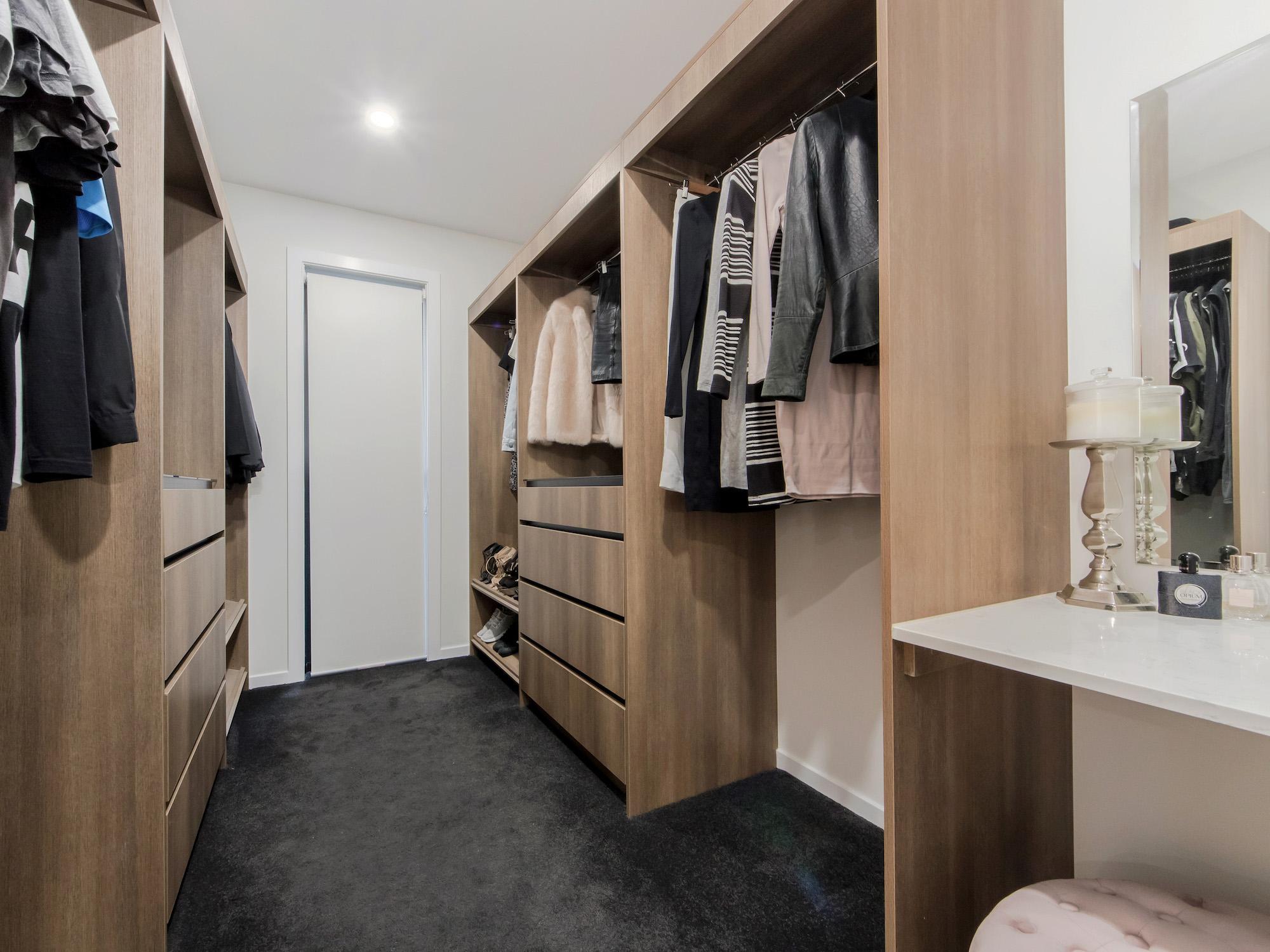 custom walk in wardrobe with vanity seating finished in Polytec sepia oak ravine
