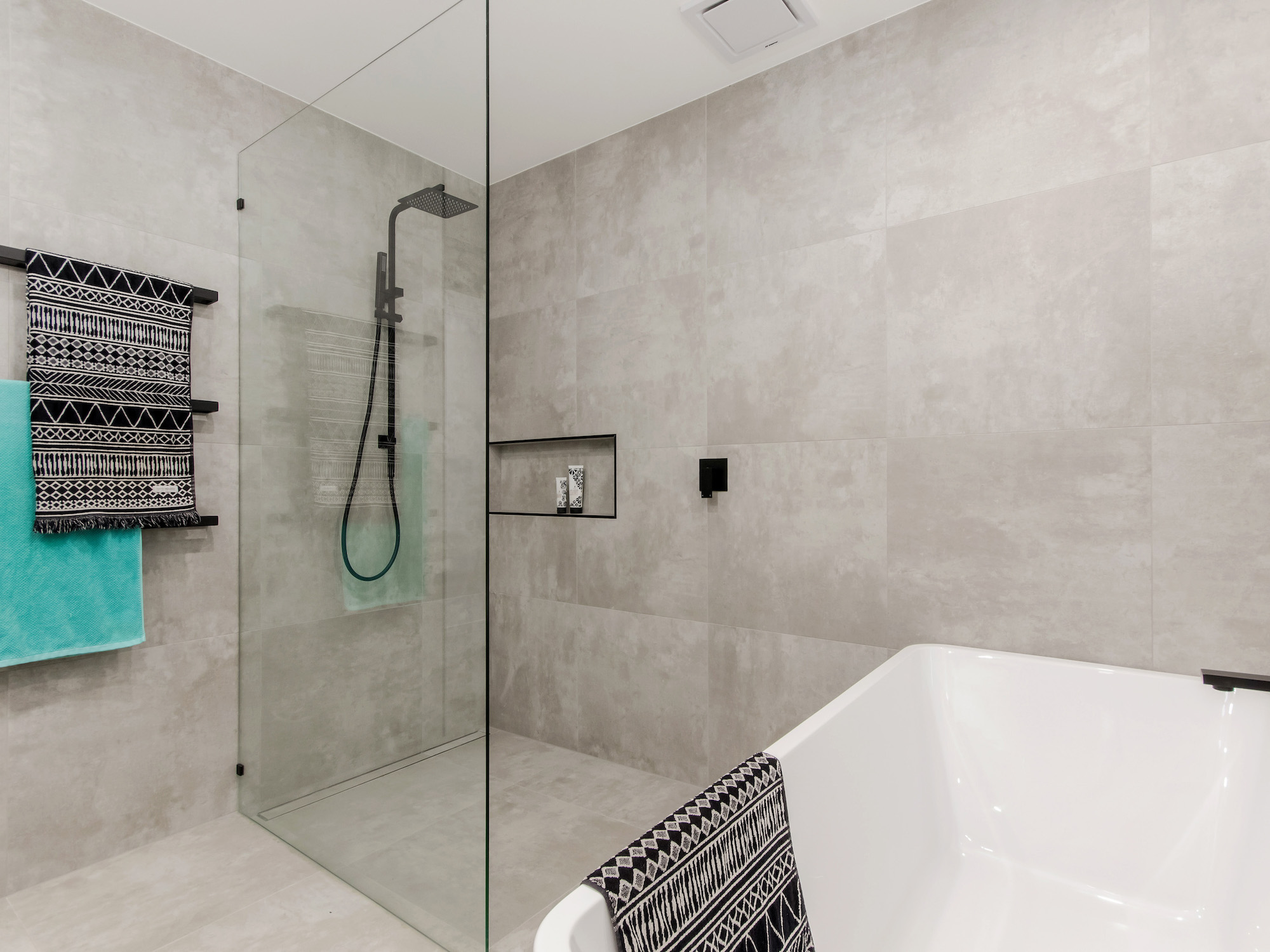 Open shower in family bathroom with concrete tiles  and matt black tap ware
