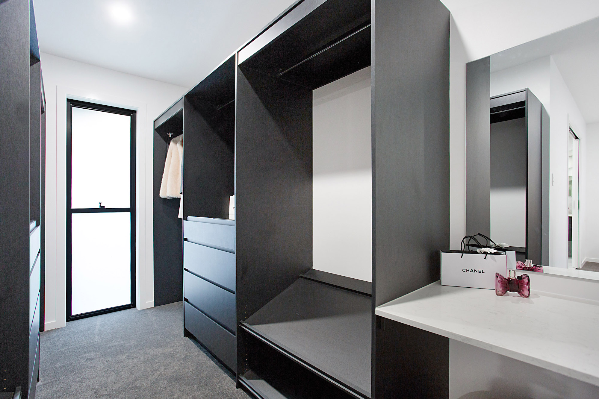 Luxury walk in wardrobe with shoe shelves and make up vanity station