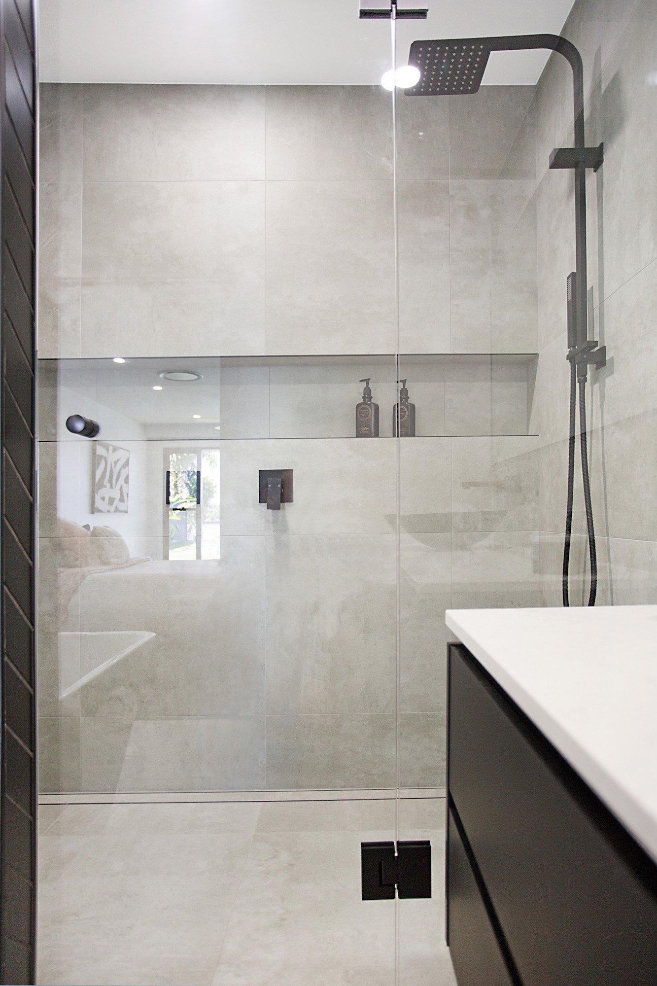 Double shower with matt black taps and concrete tiles