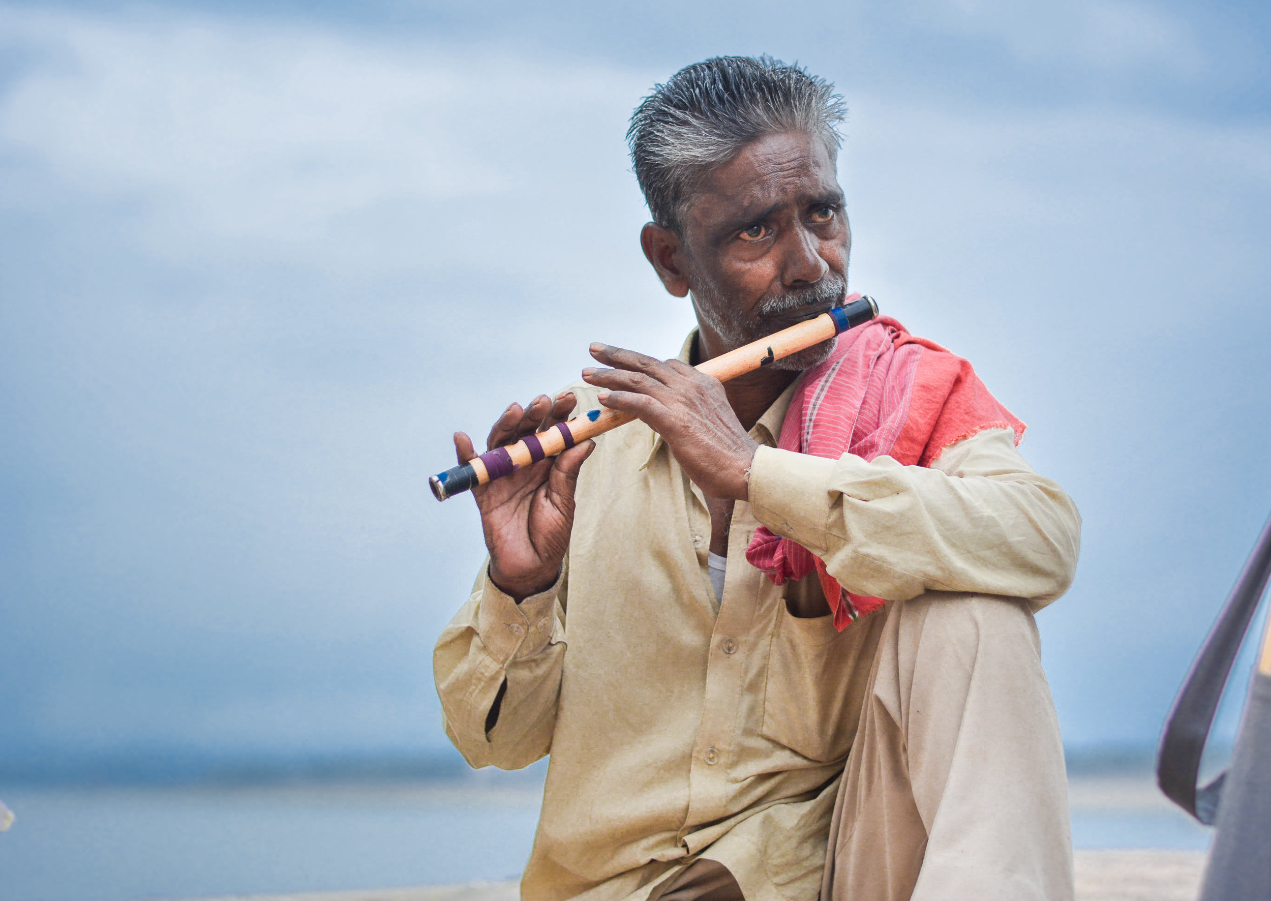 Native Asian Indian playing wooden bansuri flute.