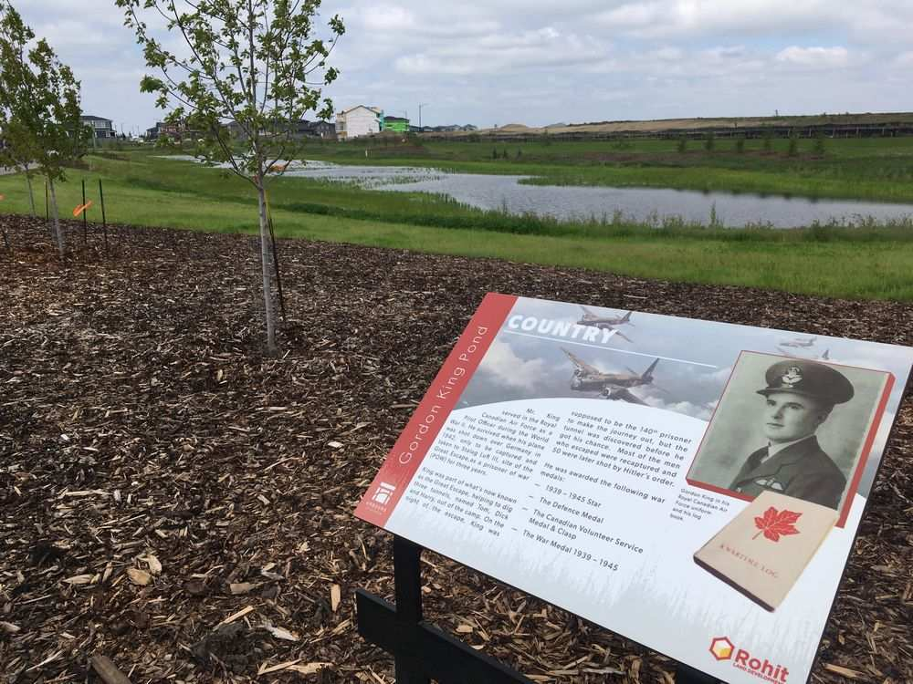 Plaques surround Gordon King Pond in the Arbours of Keswick development in southeast Edmonton. King, a 99-year-old Second World War veteran who dodged death several times during war, was honoured on Saturday as the city unveiled streets and a pond named after him.