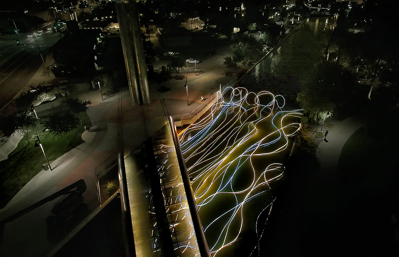 GOLDEN WATERS  Date: 2015  Media: LEDs, diffusive and reflective material, custom lighting sequence, electrical hardware  Dimensions: 40 ft x 135 ft x 18 ft Location: Soleri Bridge Scottsdale Waterfront, Canal Project | Scottsdale, AZ Credit: Courtesy of the Scottsdale Public Art/Scottsdale Cultural Council, photos by Grimanesa Amorós Studio  The ancient Hohokam Indians, located in northern Arizona, as early as 300 AD, were one of the first cultures to rely on irrigation canals. The communities environmental engineering improved access to river water and helped improve the lives of the inhabitants.  Evolving from these ideas and Inspired by the natural Arizona's canals, GOLDEN WATERS, is a large-scale temporary light-based installation. This project is mounted on the secure structures of The Soleri Bridge, located just southwest of the intersection of Scottsdale and Camelback Roads.  I was also interested of how our bodies react and are defined towards a relationship to any given environmental condition. As a result, one can feel the presence of the water and nature just by standing next to it. The piece will seemingly rise from the canal waters, as they are one with the existent canal.  The vertical and horizontal lines on the structure aim to express a metaphor that the dynamic balance between urban and natural forces can be experienced simultaneously. The viewers will be drawn to the work and will see the emphasis the piece has on its perspective of nature and landscape.