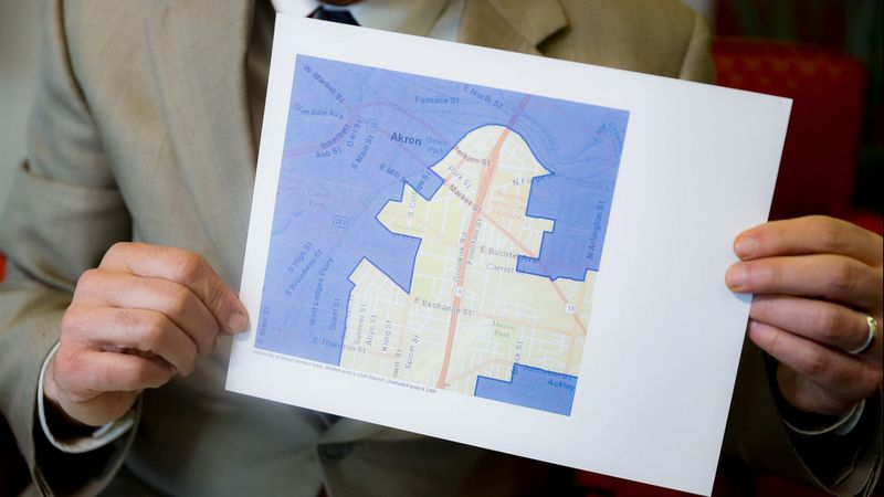 David Niven, a professor of political science at the University of Cincinnati, holds a map illustrating a gerrymandered Ohio district on April 11. (John Minchillo / Associated Press)