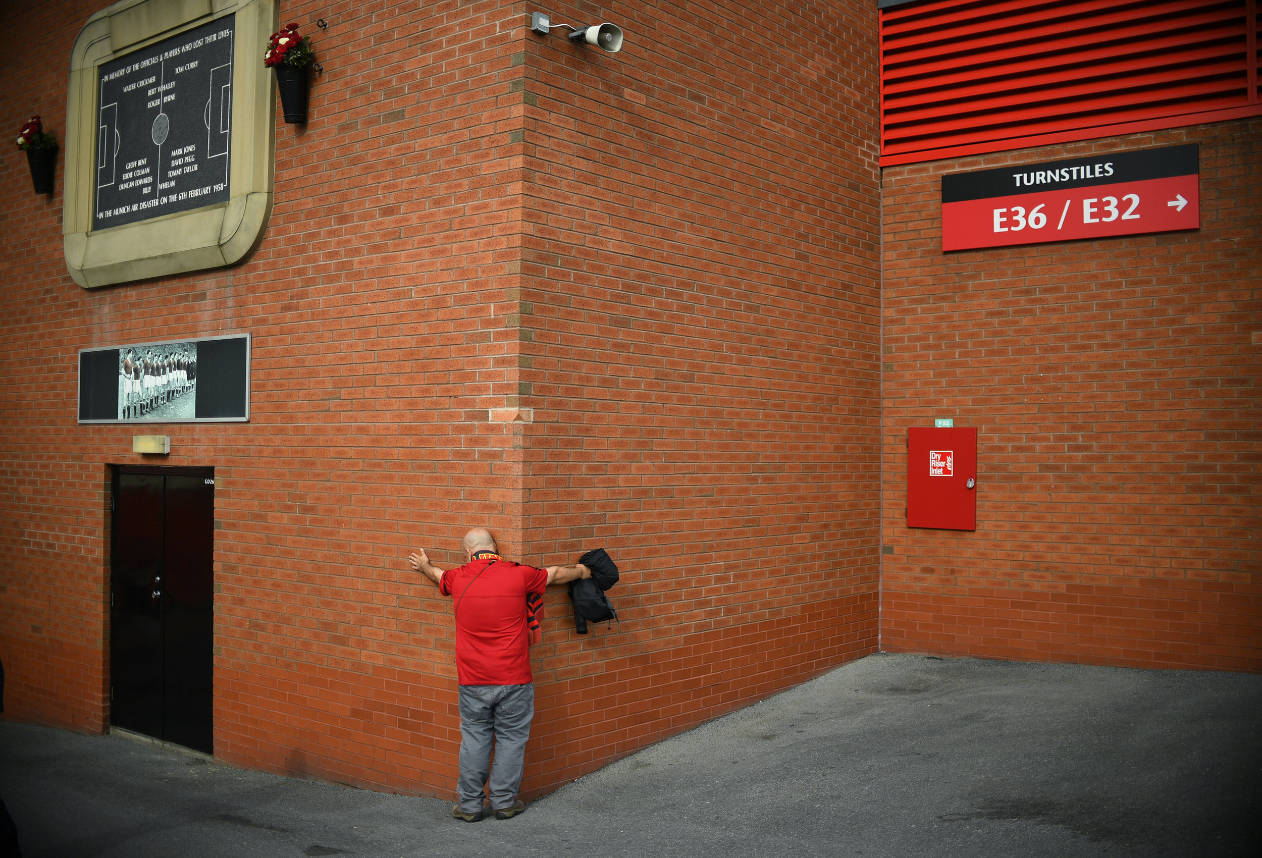 A Manchester United fan embraces the side of the Old Trafford stadium ahead of the Premier League football match between Manchester United and Leicester City.Photo by Anthony Devlin  24 September 2016