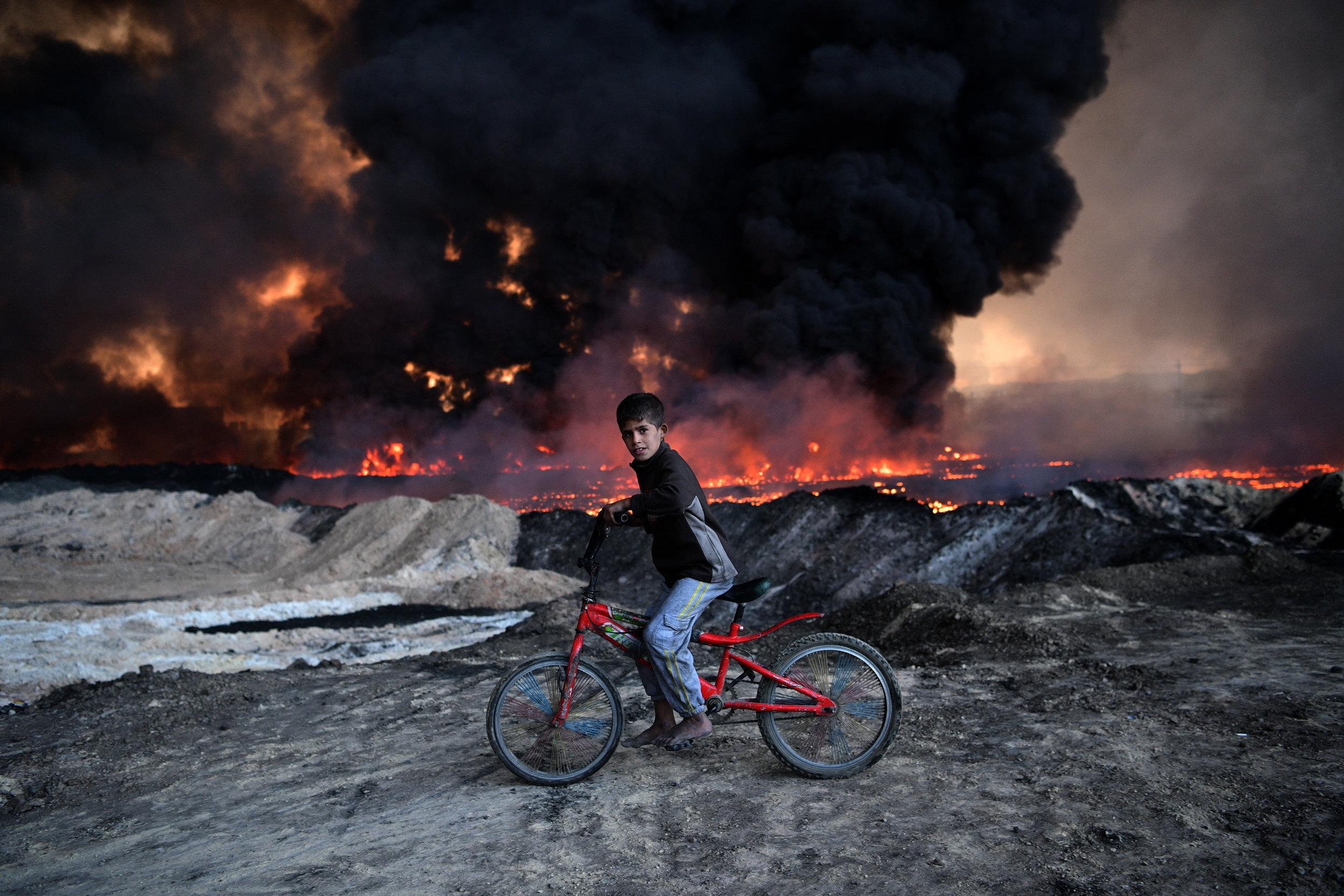 A boy pauses on his bike as he passes an oil field that was set on fire by retreating ISIS fighters ahead of the Mosul offensive in Qayyarah, Iraq.Photo by Carl Court  21 October 2016