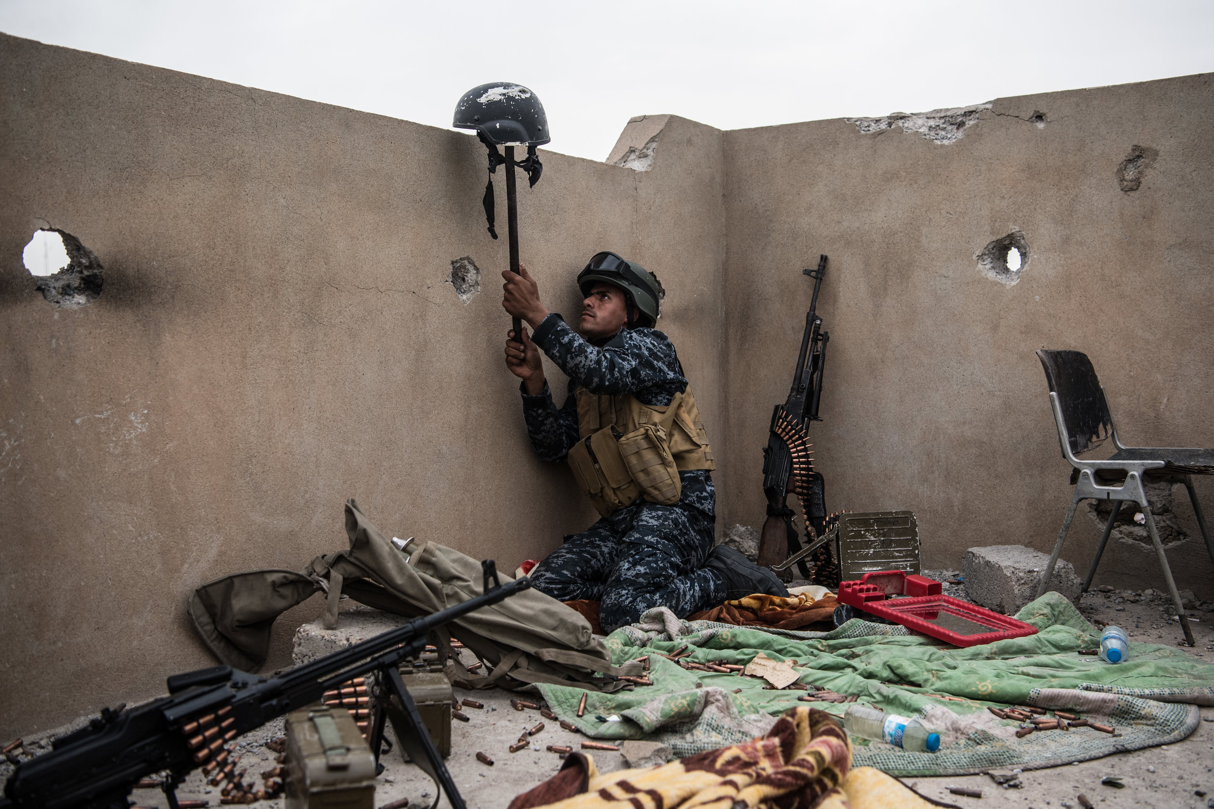 An Iraqi federal policeman uses a helmet on a stick to try and draw fire from an Islamic State sniper in an attempt to make him reveal his position during the battle to recapture west Mosul, Iraq�s second largest city.Photo by Carl Court  13 April 2017