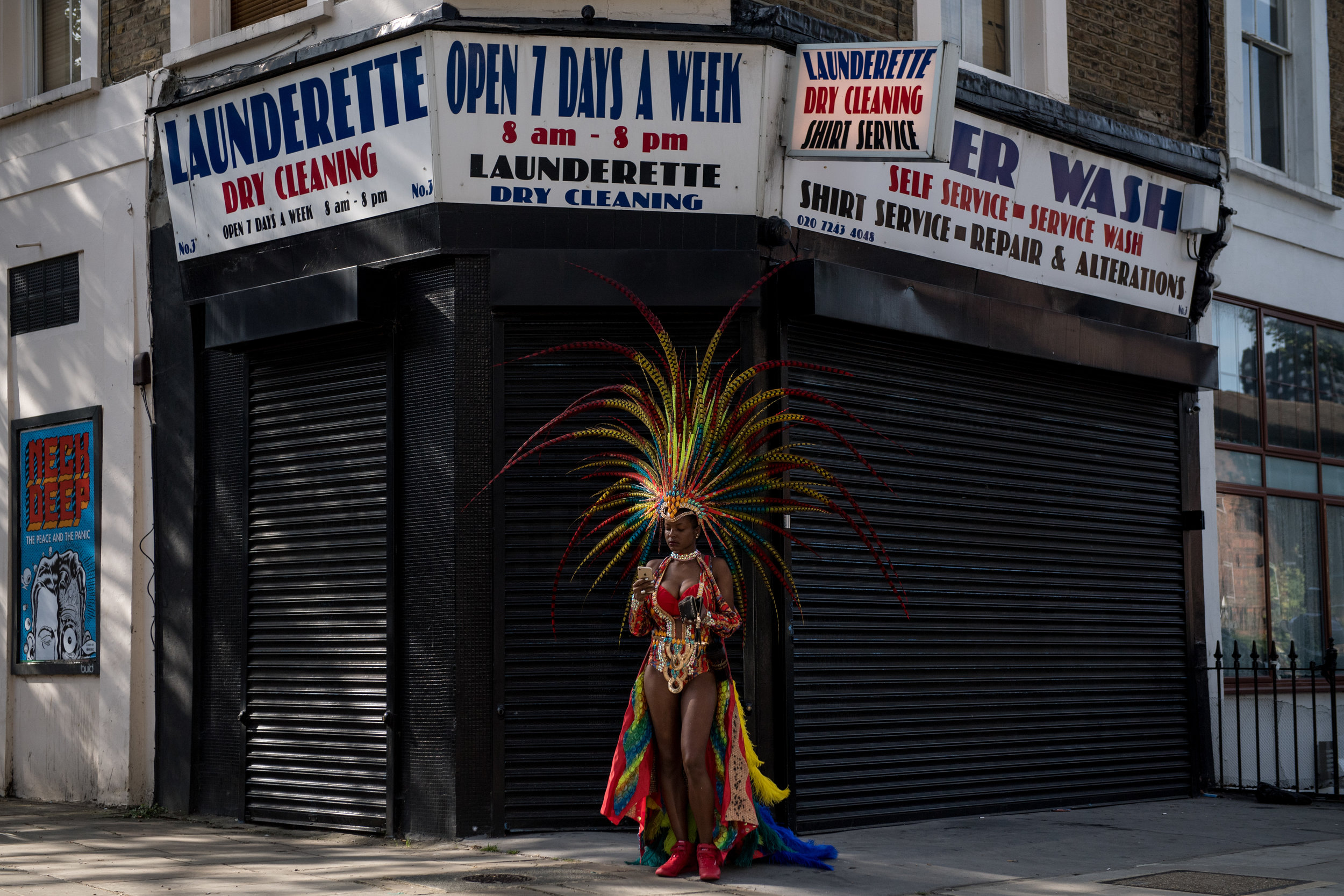 A performer looks at her phone outside a launderette before the start of the Notting Hill Carnival parade.Photo by Chris J Ratcliffe  28 August 2017