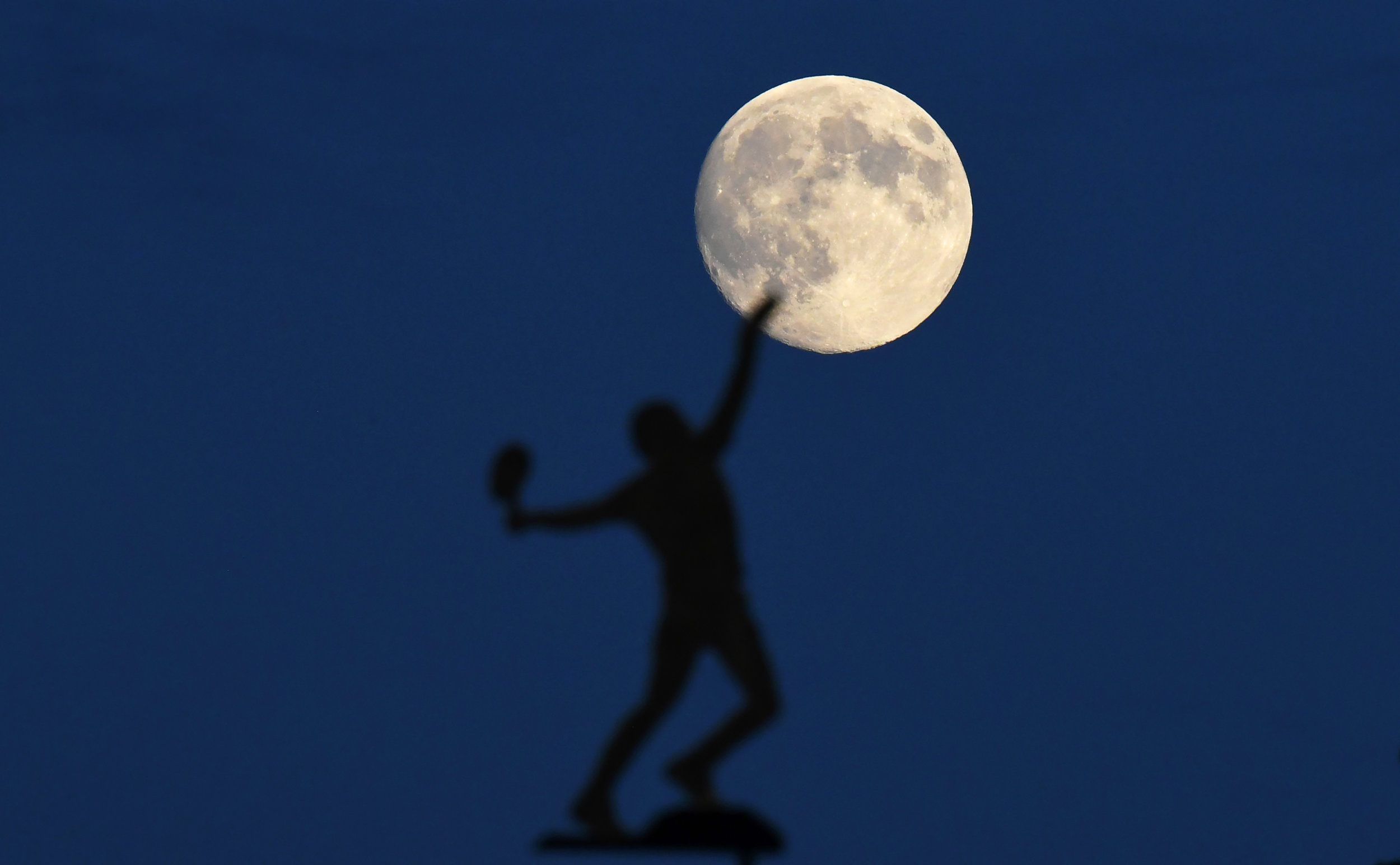 The almost full moon rises behind the weather vane at the All England Lawn Tennis Club at Wimbledon during The Championships.Photo by Facundo Arrizabalaga  17 July 2017