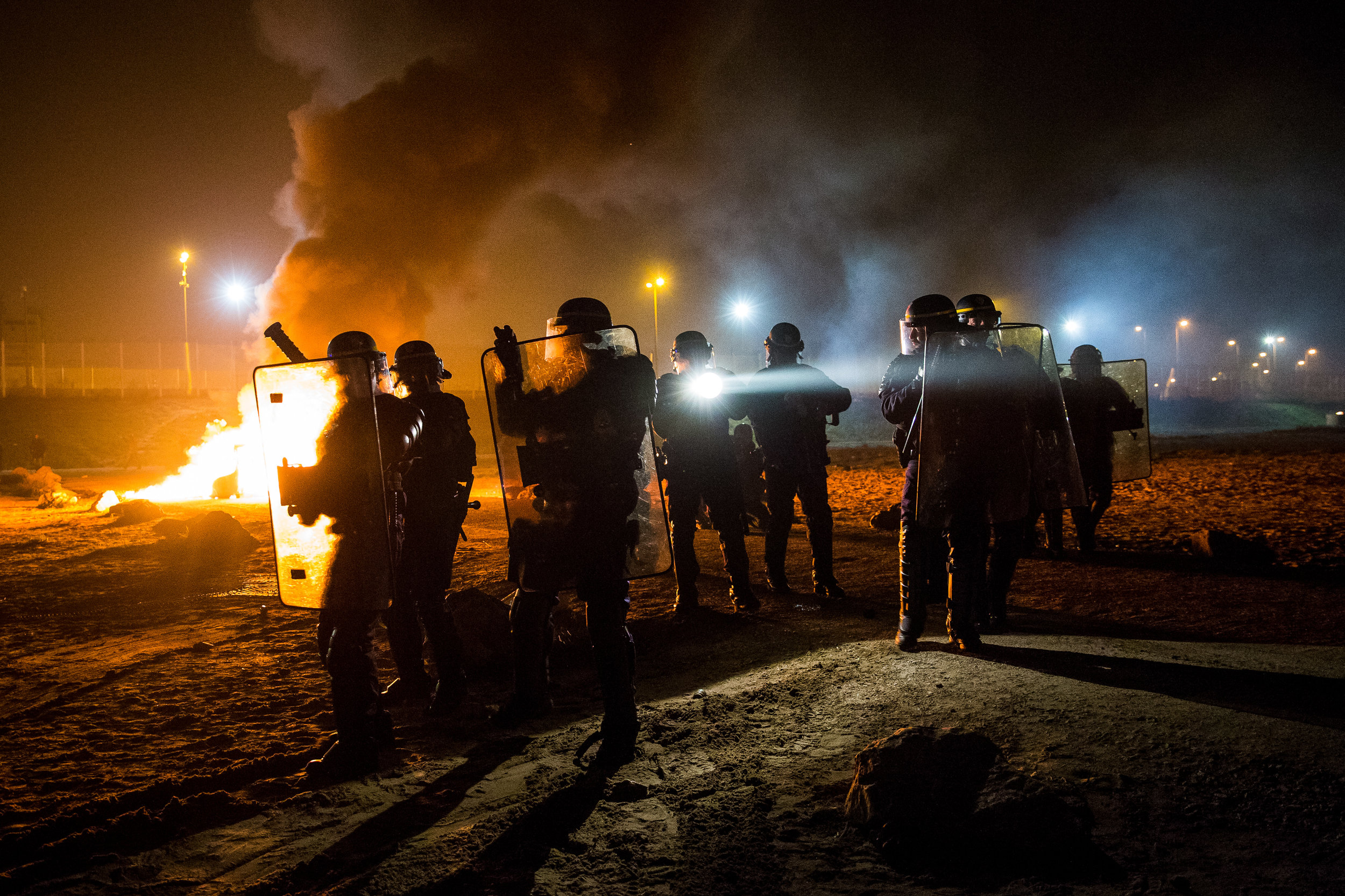 A portable chemical toilet burns as French riot police advance towards the Jungle migrant camp during a clash with migrants just outside Calais.Photo by Jack Taylor  23 October 2016