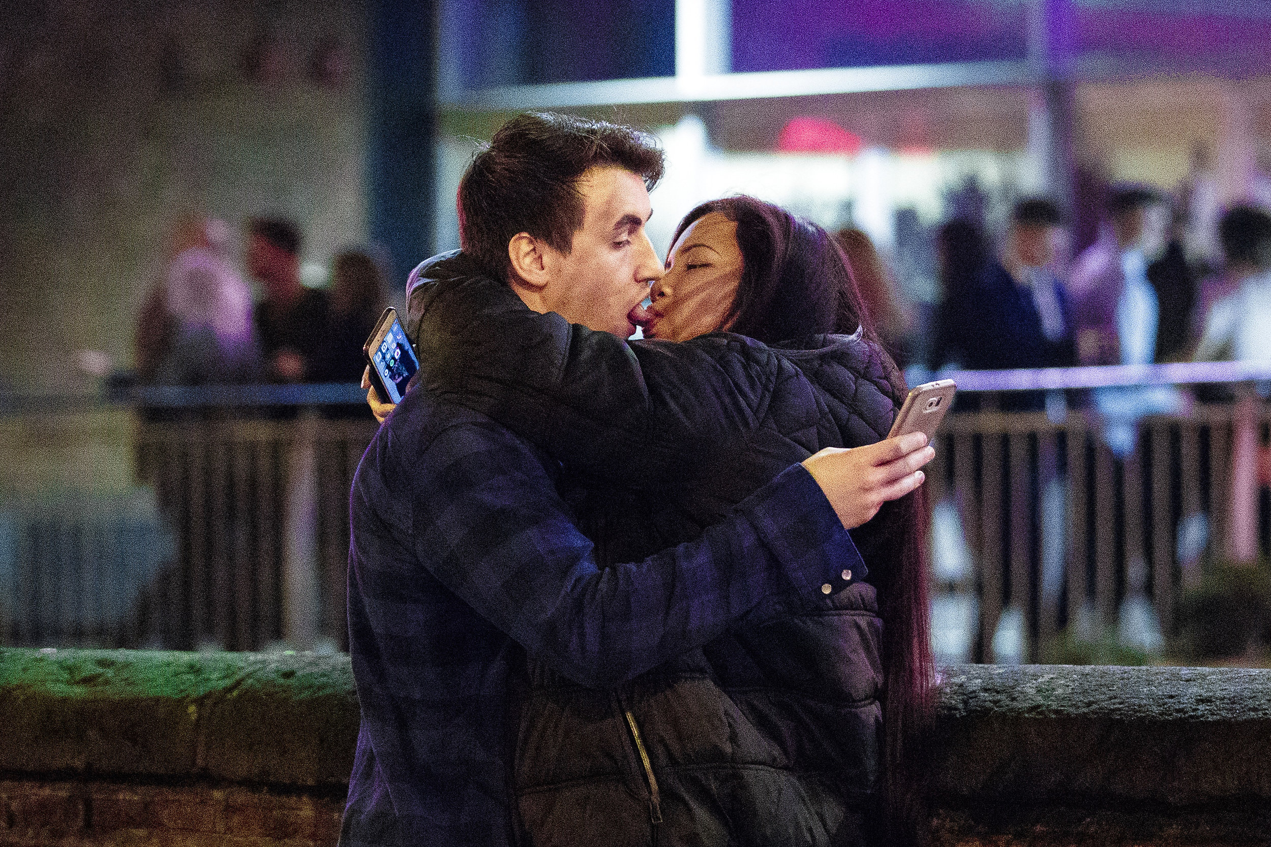 """A couple embrace and French kiss whilst operating their mobile phones during a pre-Christmas """"Mad Friday"""" night outside bars at Deansgate Locks in Manchester City Centre.Photo by Joel Goodman  17 December 2016"""