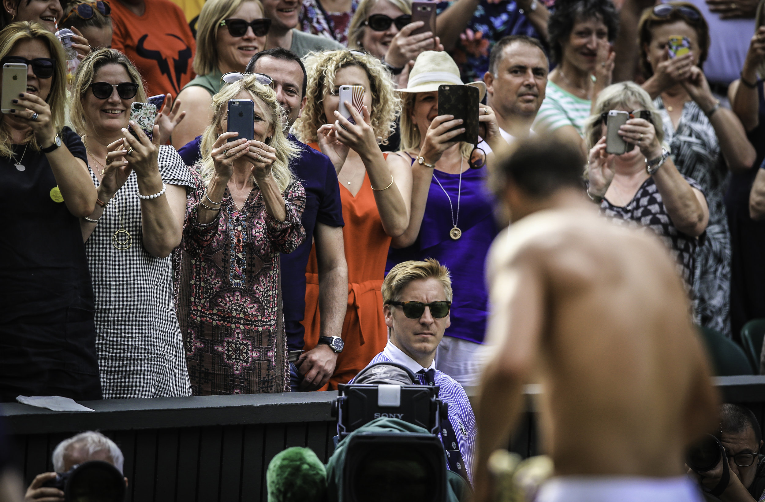 Female spectators take pictures of Rafael Nadal of Spain as he changes his shirt after a match on Wimbledon�s Centre Court during The Championships.Photo by Lindsey Parnaby  07 July 2017