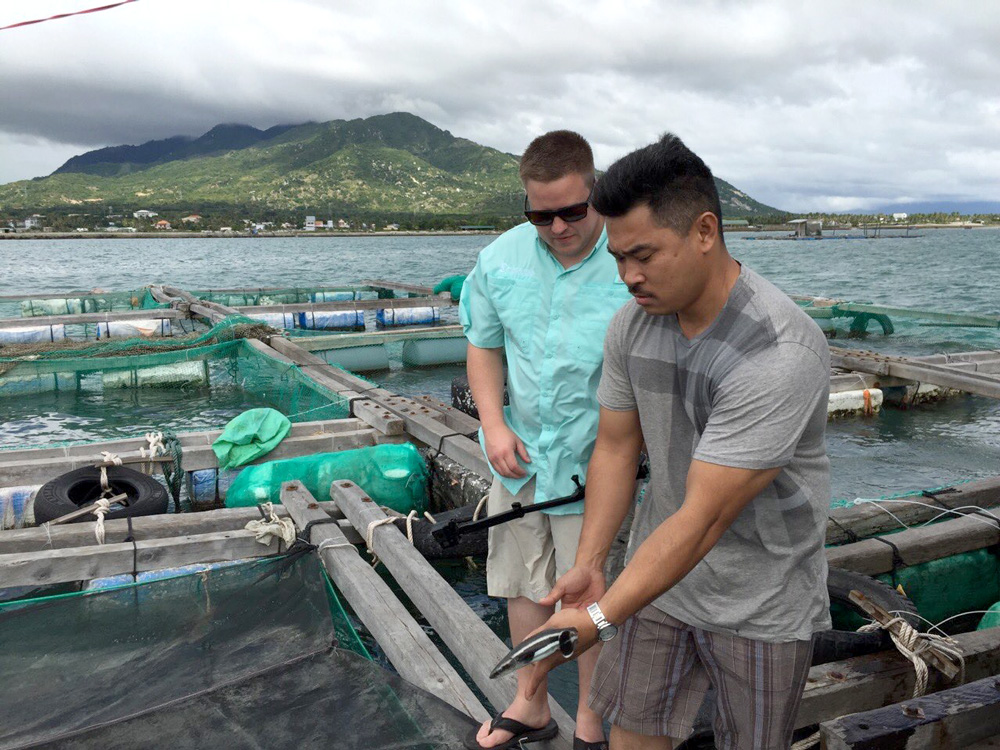 Luke Keeton fishing with our customer at a cage culture environment in Vietnam