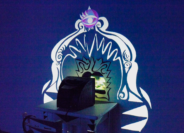 """In """"Prom Girl's Vanity"""", a TV placed on a customized vanity table facing a mirror shows a secret video only viewable from certain angles. The video image is framed by an illustration, which is then framed by a projection. The video playing on the TV is a mini-musical called """"Shadow of a Woman"""", in which Prom Girl awakens in the middle of the night to find Gold Dust Woman serenading her over a midi track."""