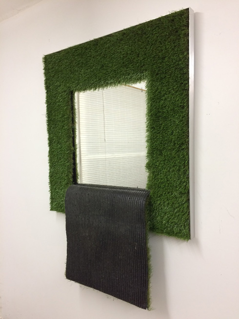 "The Grass is Always Greener - A square flap of artificial turf has been cut and allowed to hang down revealing its utilitarian underside. As we look into the mirror framed by the green grass we are confronted with this dark underside.Materials: Artificial Turf, Mirror, Aluminum FrameDimensions: 60"" x 42"" x 4"""