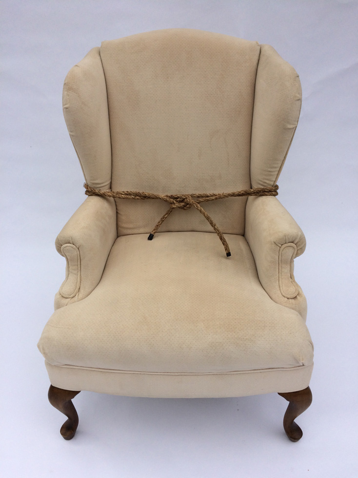 "Bound Chair - This piece consists of an old easy chair upholstered with worn ivory velvet. Shaped for a user's support and relaxation, the chair's back, arms, and legs mirror the human form it serves. In this case, however, the chair is no longer easy. Arms tightly bound with rope, it cannot comfort others or itself. Copyright Jamie Calderwood 2018 Materials: Wingback easy chair and ropeDimensions: 30"" x 30"" x 42"" Ht."