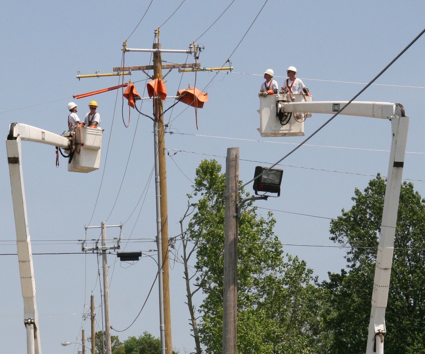 electrical companies in bucket trucks doing some telephone pole maintenance