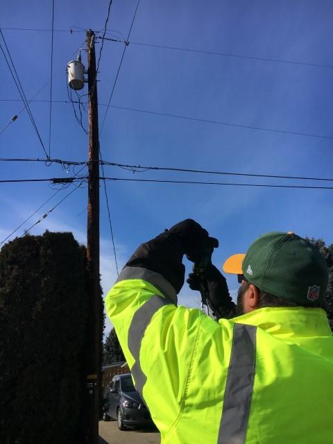 Washington broadband employee taking pictures of a telephone pole