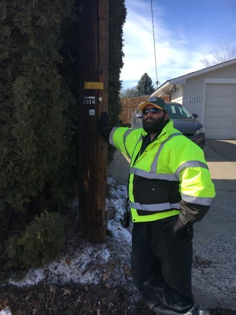 Washington broadband employee standing beside a telephone pole.