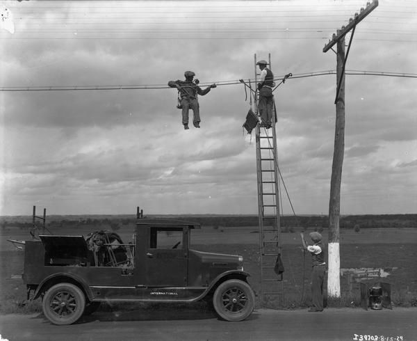 black and white photo of people doing telephone wire maintenance