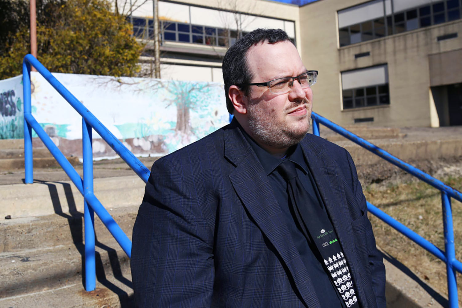 Steven Singer is a teacher at Steel Valley Middle School. Here he is photographed outside White Oak Elementary School, where he attended as a child. The school closed in recent years. (Photo by Ryan Loew/PublicSource)