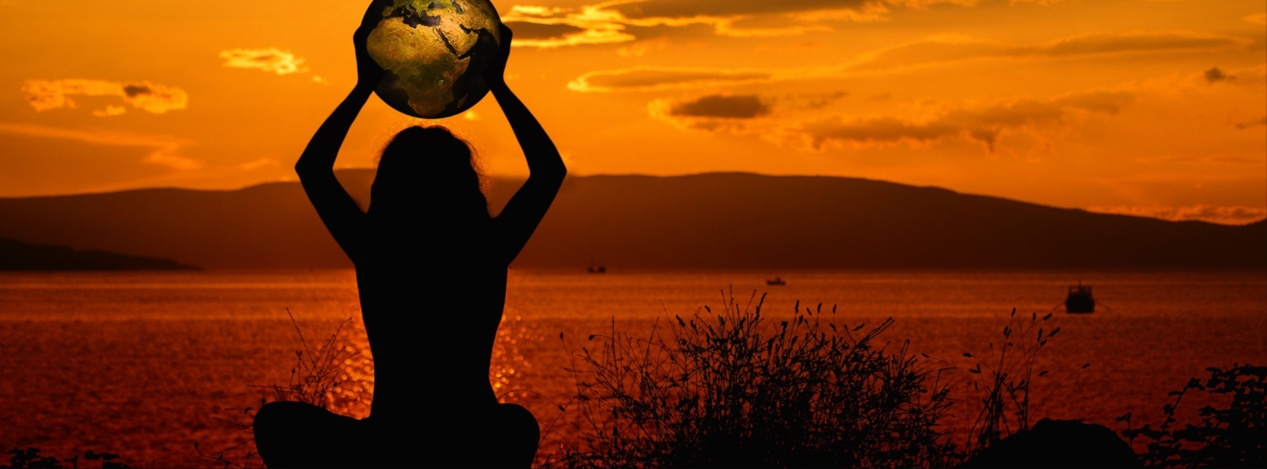 woman sitting holding globe to sky at sunset.png