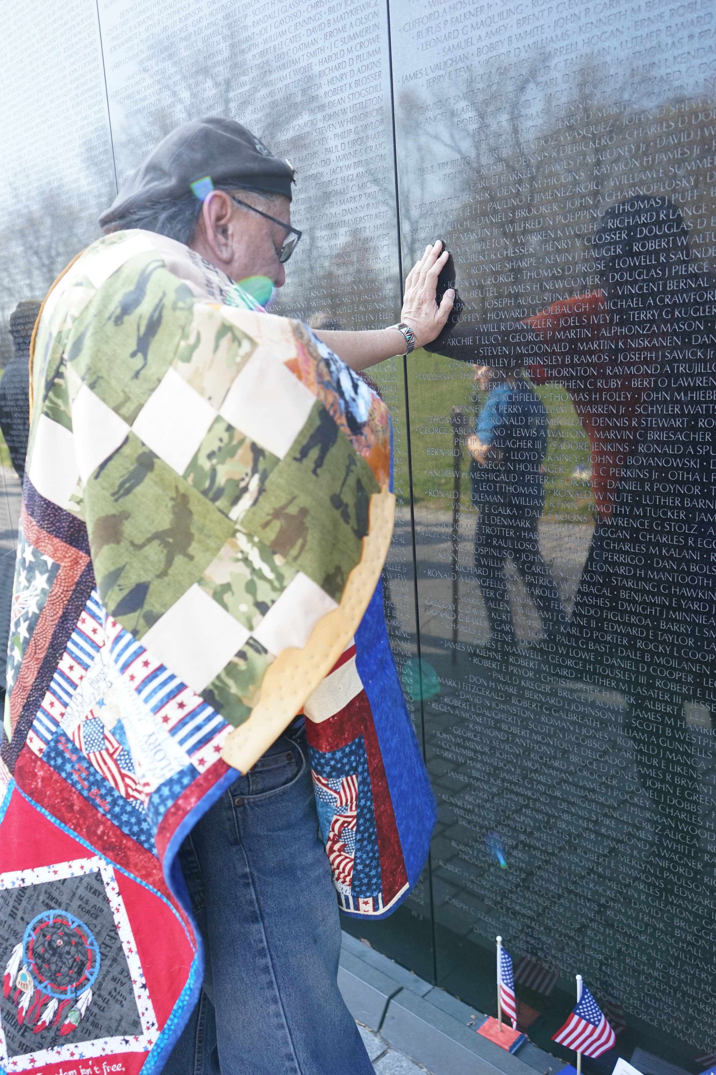 Mending Souls supports veterans by wrapping them in elders' shawls to honor their service. A shawl was presented to the veteran pictured above as he searched the names of his fallen at the Vietnam Wall in Washington, D.C.