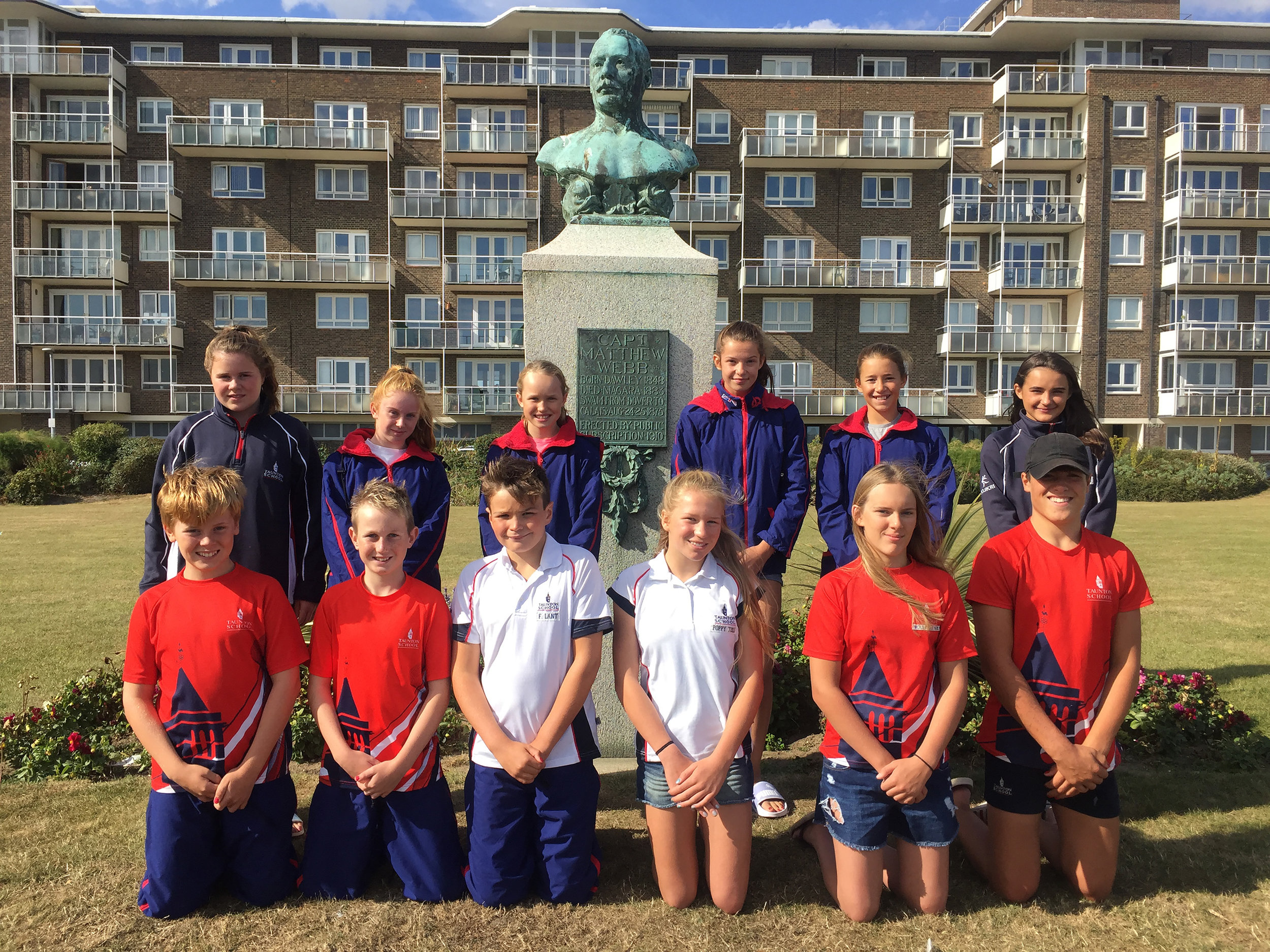 Taunton School Swimmers in front of statue of William Webb, first man to swim the Channel
