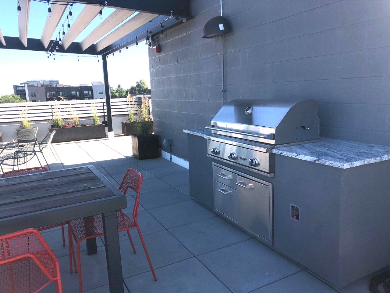 Community grill and fire pit at OB Flats Roof deck.