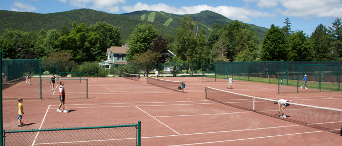 Set at the base of the mountains in a scenic valley, the Waterville Valley Tennis Center has been delighting tennis enthusiasts of all abilities for 134 years. With eighteen outdoor clay tennis courts and two indoor courts, the Tennis Center has the facilities, instruction, staff and setting to make your tennis adventure a memorable one. Since 2001, Tennis Resorts Online has ranked Waterville Valley Tennis in the Top 25 best-in-the-world, along with a #2 ranking for Best Setting and a #4 ranking for Best Kids Programs and Best Value.