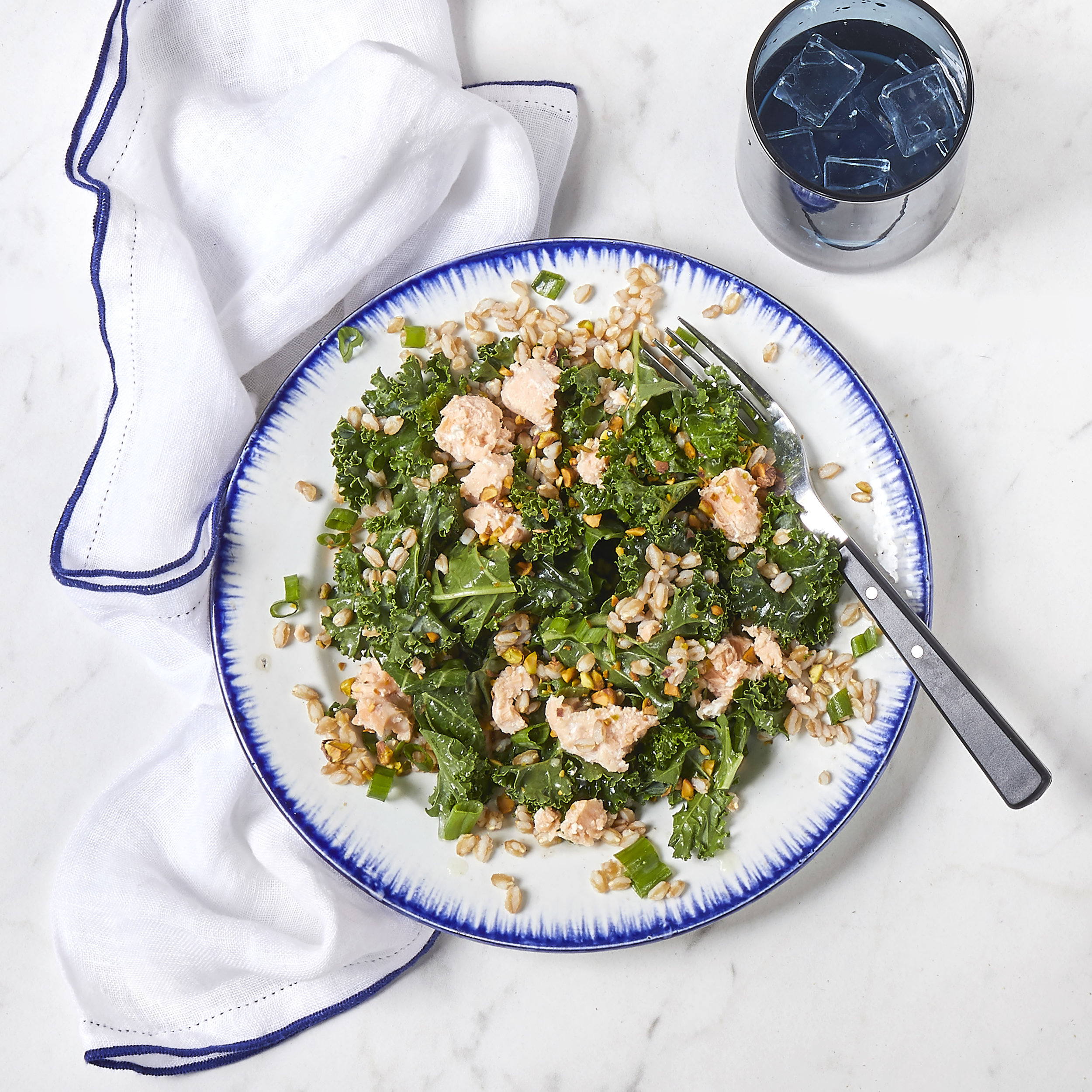 Kale Farro Salad with Salmon - Ingredients:- Juice of Half a Lemon- 2 Tbsp Extra Virgin Olive Oil- Course Salt & Freshly Ground Pepper- 2 Tins of Cole's Patagonia Salmon in Spring Water- 1 Bunch of Scallions, Thinly Sliced- 1 Bunch of Kale, Cut into 1-2 inch Pieces- 1/2 Cup of Flat Leaf Parsley- 1 Cup of Cooked Farro (cooked to package instructions)- 1/2 Cup PistachiosDirections:In a medium bowl, whisk together the lemon juice and olive oil. Season to taste with salt and pepper. Toss together the kale, scallions, parsley, and farro. Top with the salmon, dressing, and pistachios.