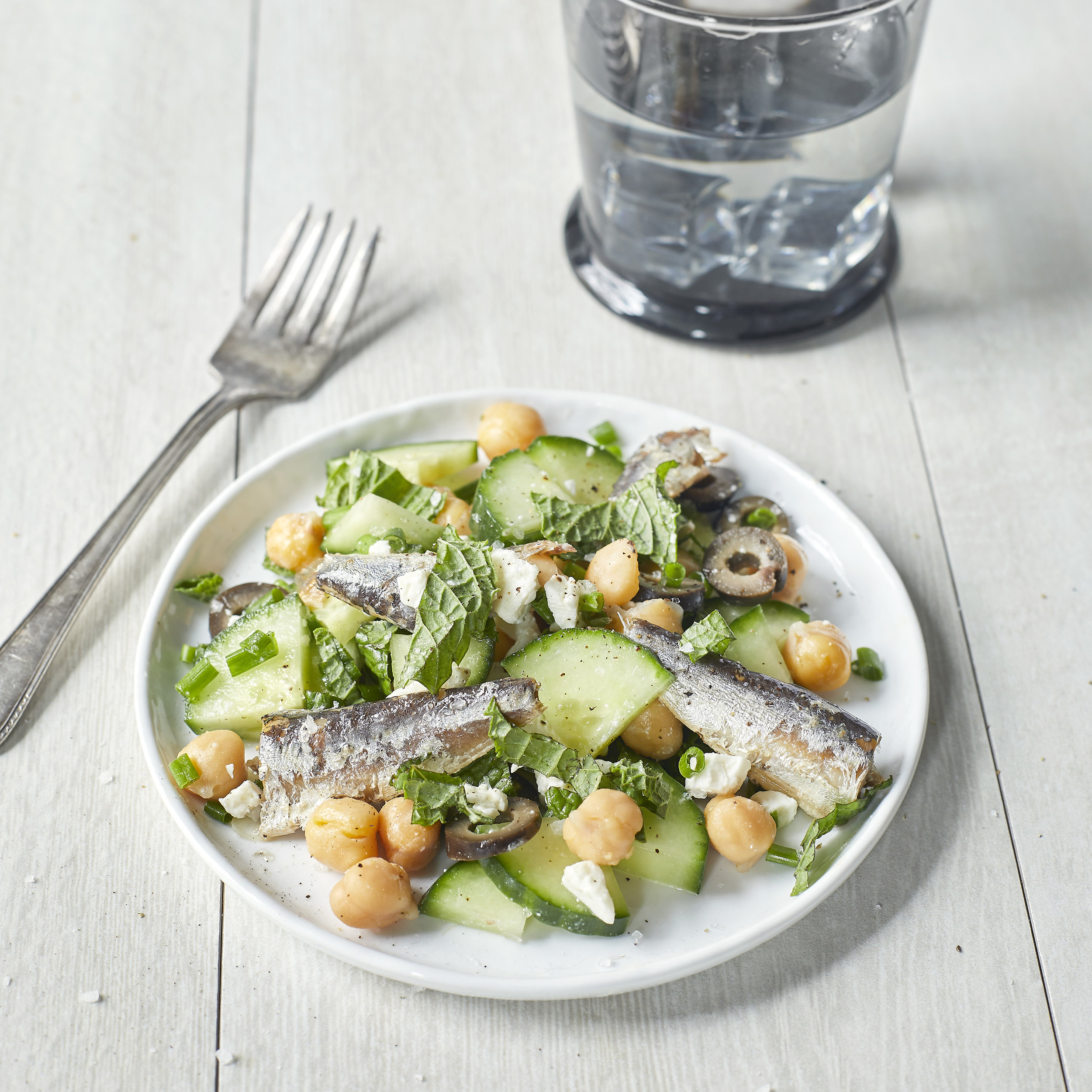 Sardine Salad with Chickpeas & Feta   - Ingredients:- 1 16oz Can Chickpeas, rinsed and drained - 2/3 Cups Cucumbers, seeded & diced - 2 Tins of Cole's Petite Sardines in olive oil - 1/2 Cup Crumbled Feta Cheese - 1/2 Cup Pitted & Sliced Black Olives - 1 Tbsp Chopped Mint Leaves - 1 Tbsp Chopped Chives - 1 Medium Lemon, zest & juiced- 1 Tbsp Olive Oil - Cracked Black PepperDirections:In a medium bowl, stir together chickpeas, cucumber, feta, olives, lemon zest and juice, mint, and the olive oil. Arrange 2-3 fillets on each salad and sprinkle with a pinch of chopped chives and a few cracks of black pepper.