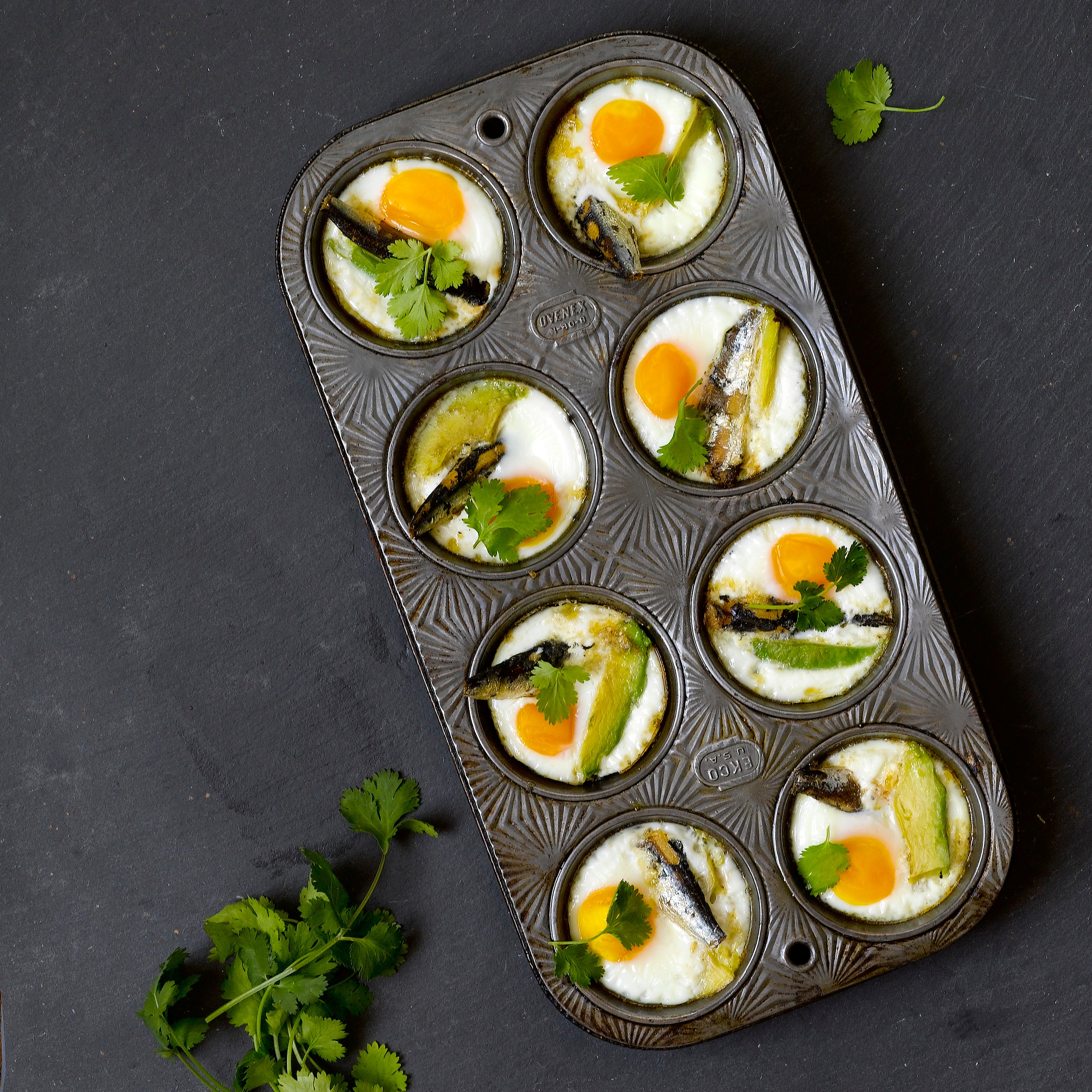 Petite Sardine Baked Eggs - Ingredients:- 8 Eggs- 1 Ripe Avocado- 1 Small Bunch of Fresh Parsley- 2 Tins of Cole's Petite Sardines- Pinch of Salt and Pepper for Each EggDirections:Crack one egg into each muffin tin cup. Add one or two slices of avocado to each cup (be sure to cover with egg white if exposed to avoid any browning of the avocado). Drop 1-2 Petite Sardines into each cup, sprinkle with salt and pepper, and top with fresh bits of parsley. Pop into the oven for 9-12 minutes at 375 degrees (depending on how well you like your eggs cooked). Let cool 5 minutes and enjoy!