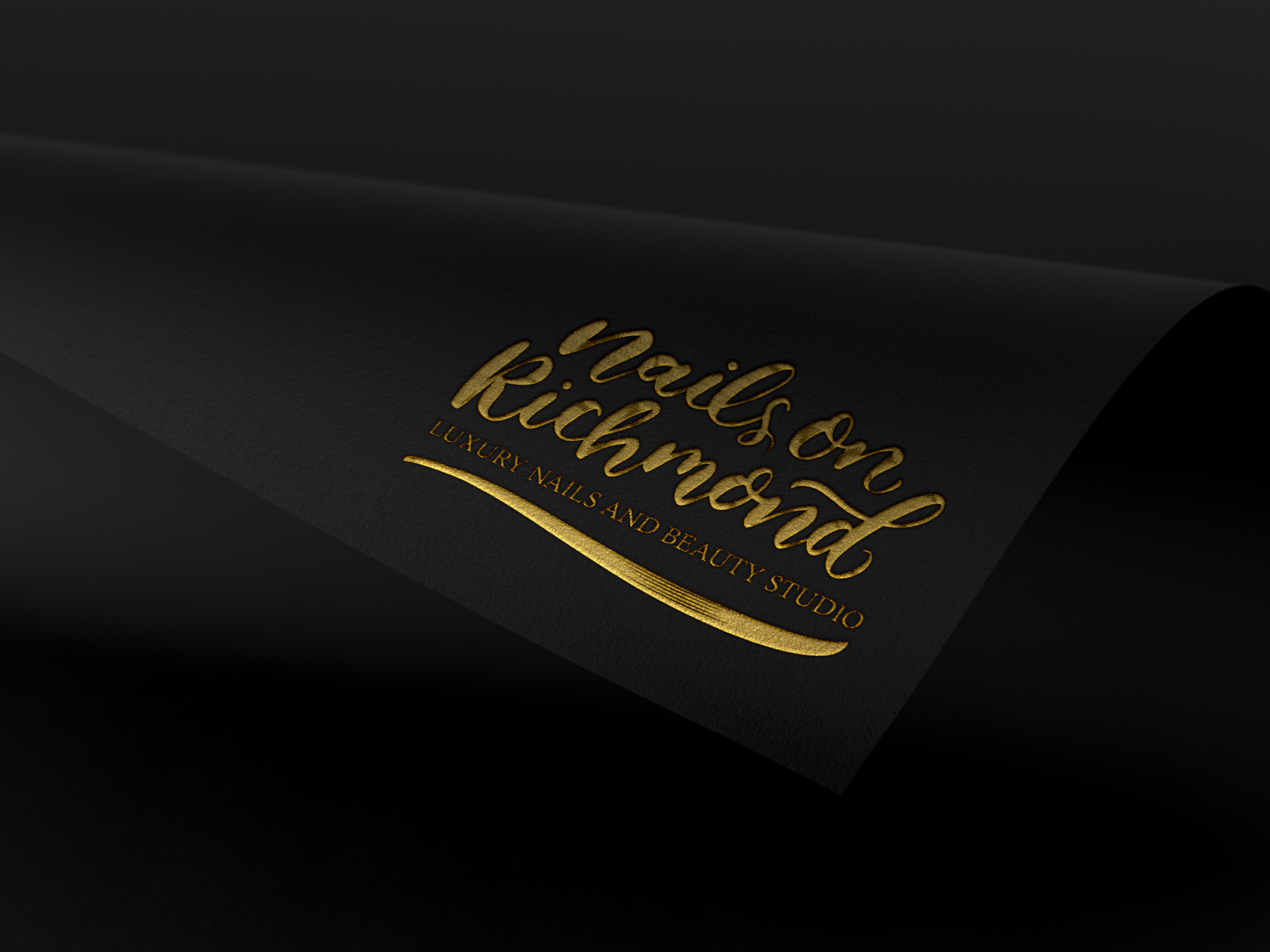Folded black paper with a gold embossed logo