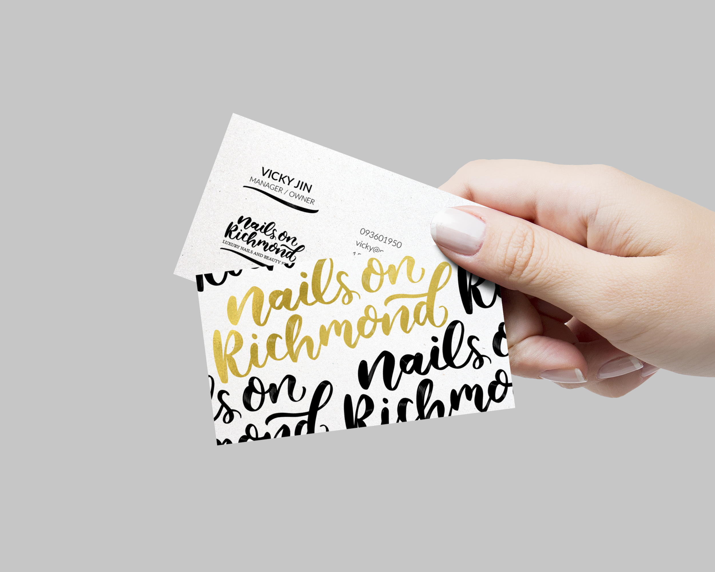 Hand holding two business cards