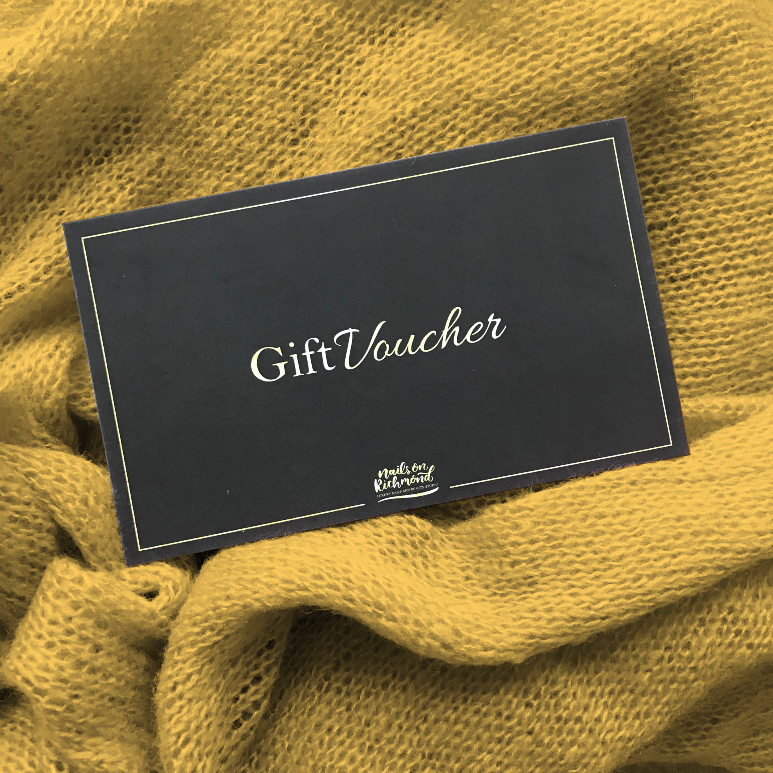 Black gift Voucher placed on a mustard throw
