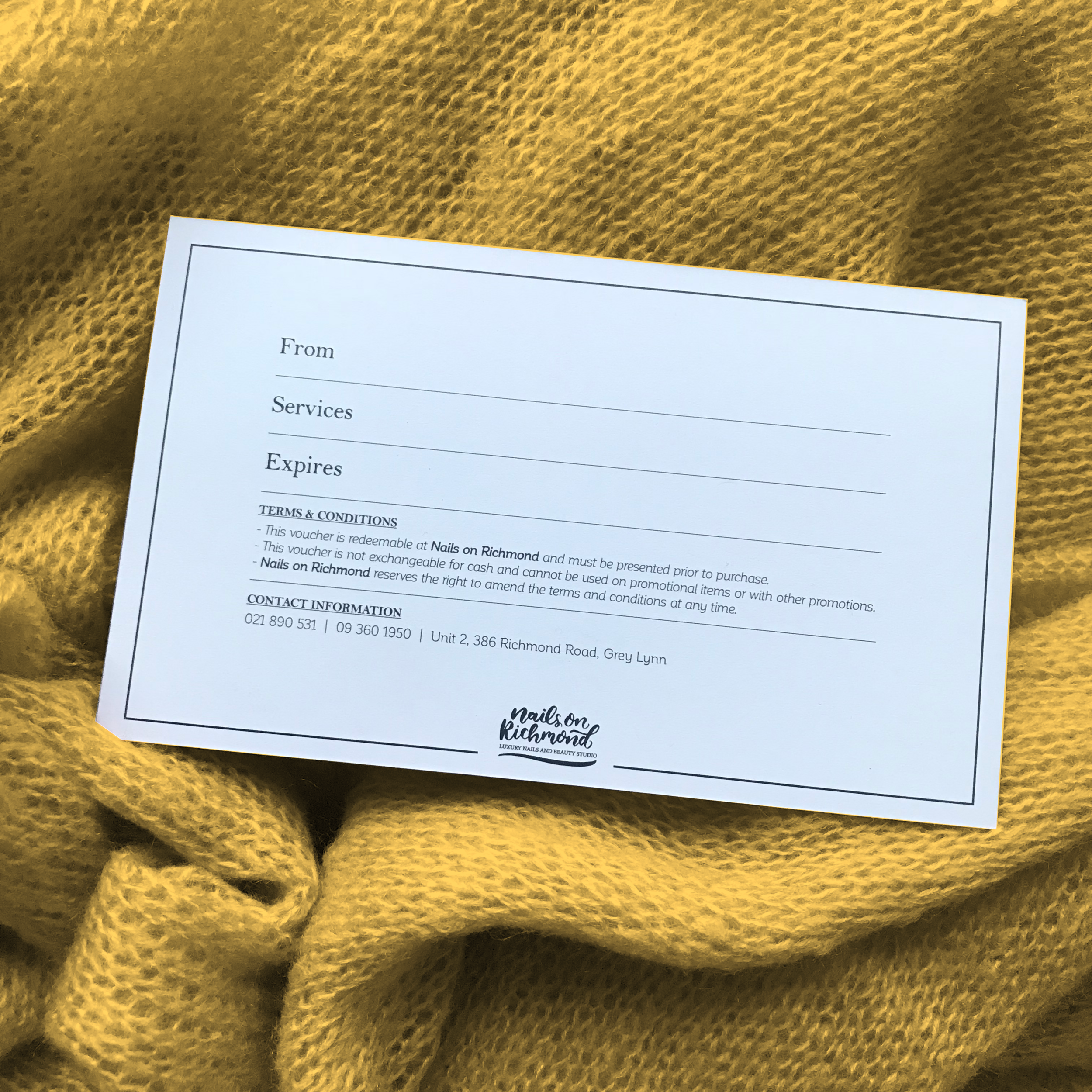 Gift voucher placed on a mustard throw