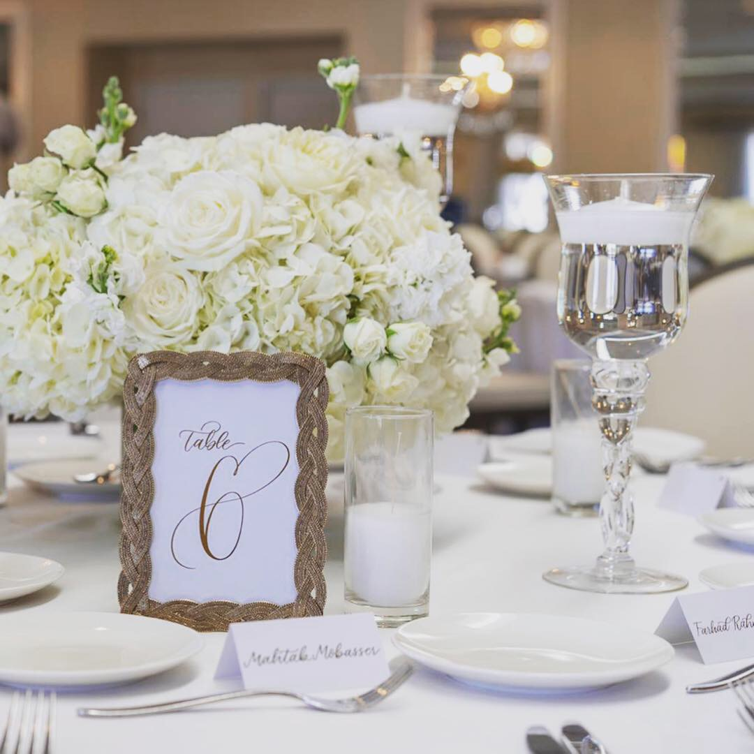 Wedding table arrangement with table number and place cards
