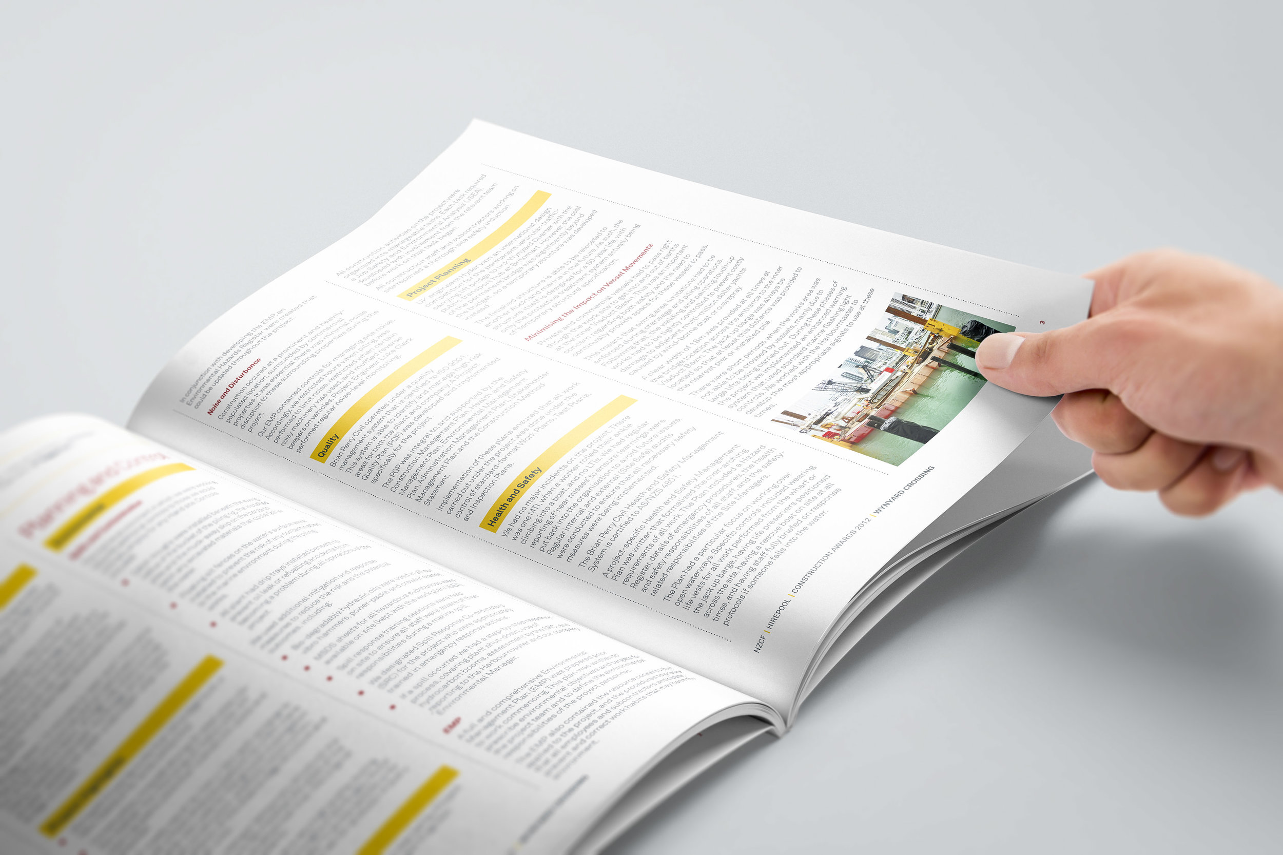 A hand  flipping through an open brochure placed on a table