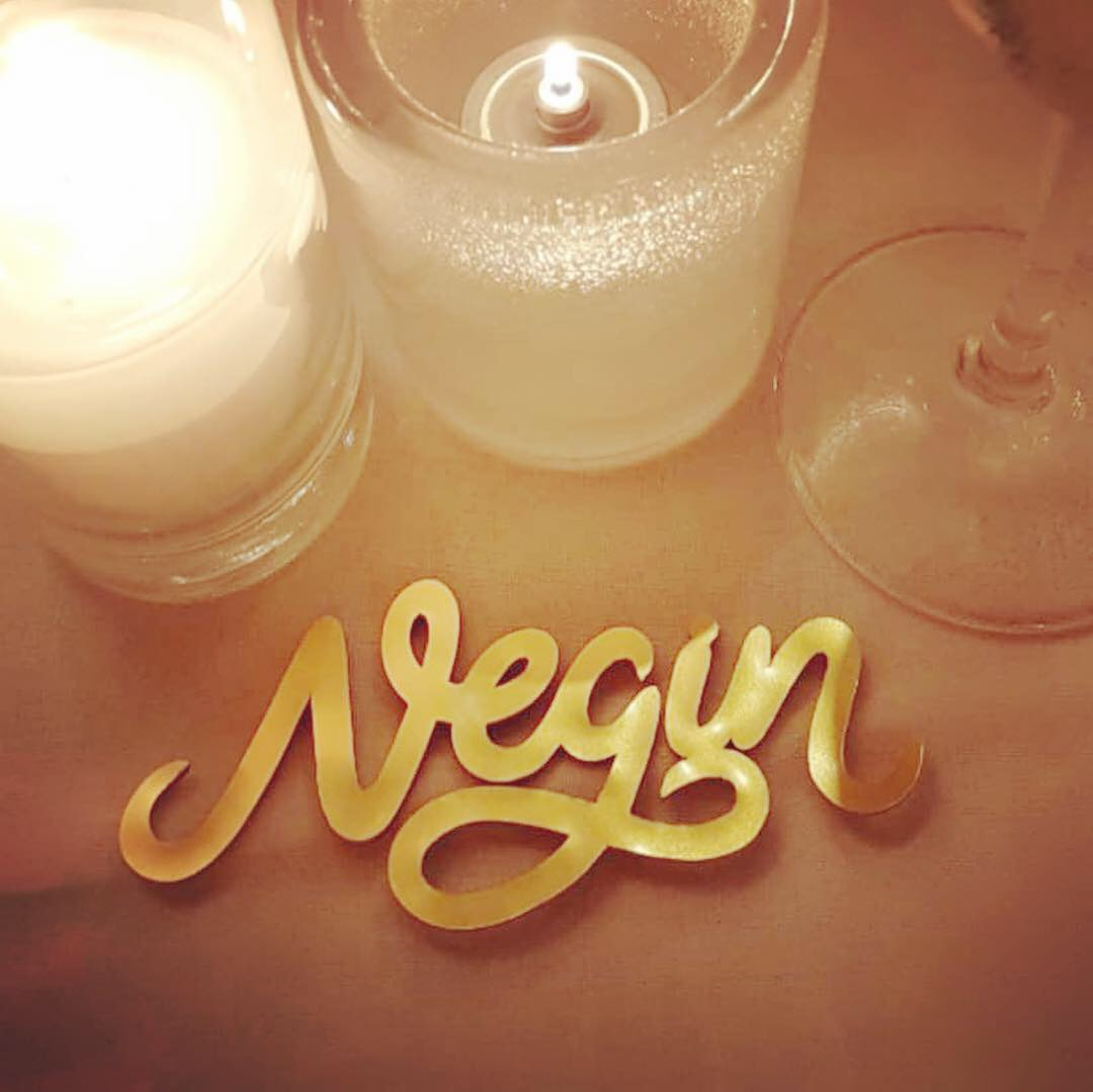 A gold cut out name on a table next to candles