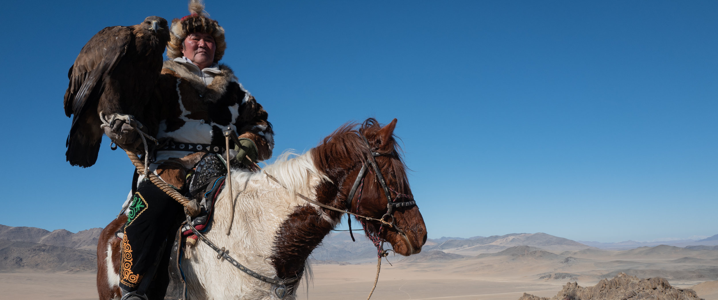Eagle Hunter, Sailau, on horseback with his Golden Eagle