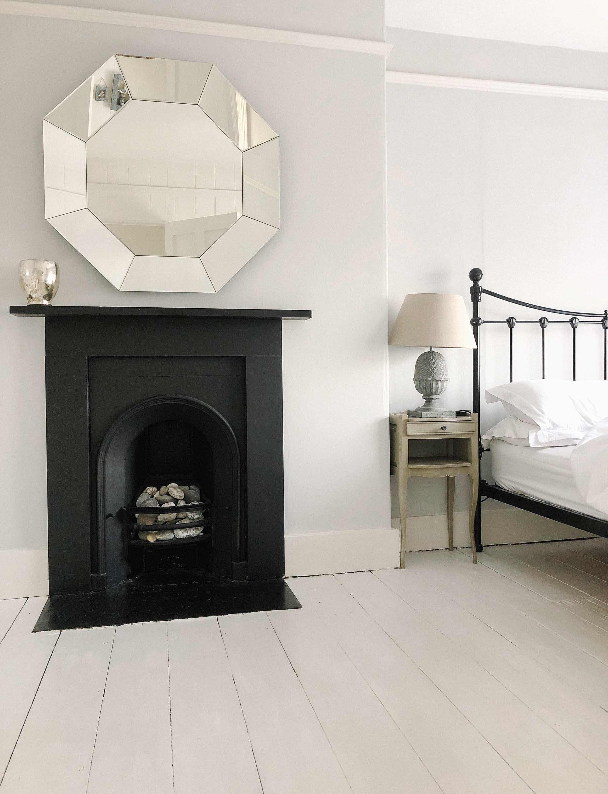 19 white washed cottage bedroom with black fireplace.jpg